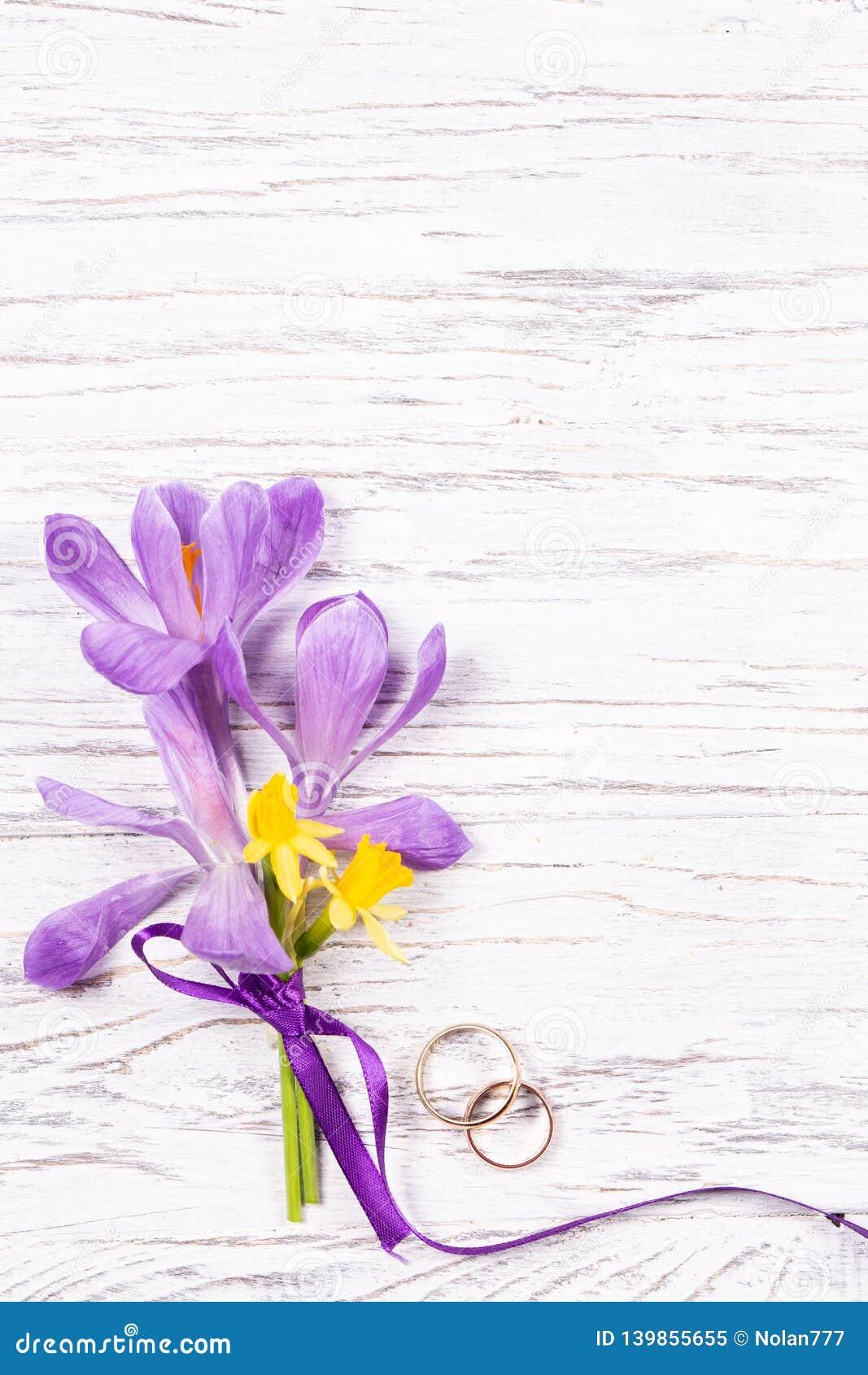 Conceito do casamento com flores da mola e dois anéis dourados