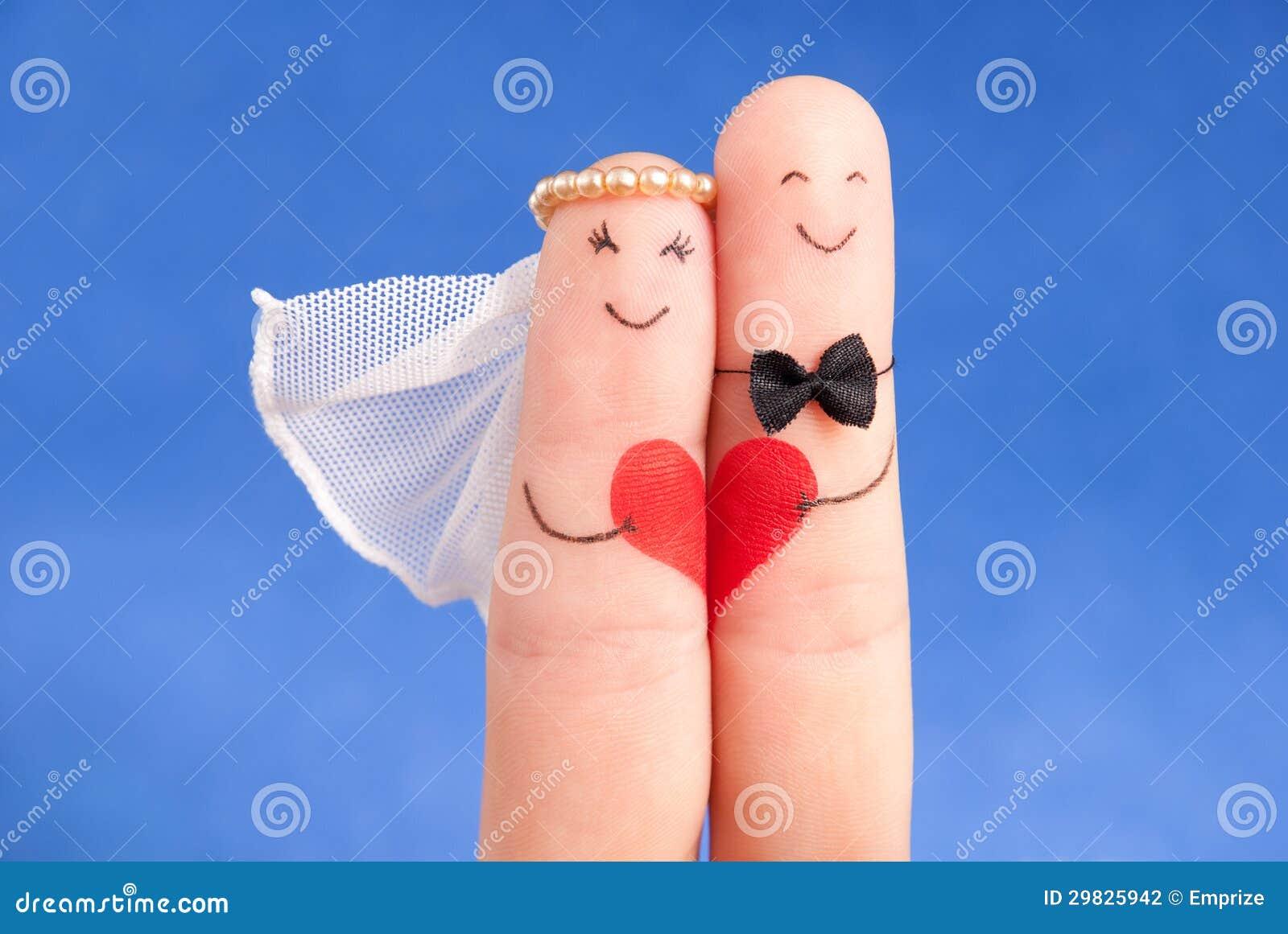Conceito do casamento - newlyweds pintados nos dedos contra o céu azul