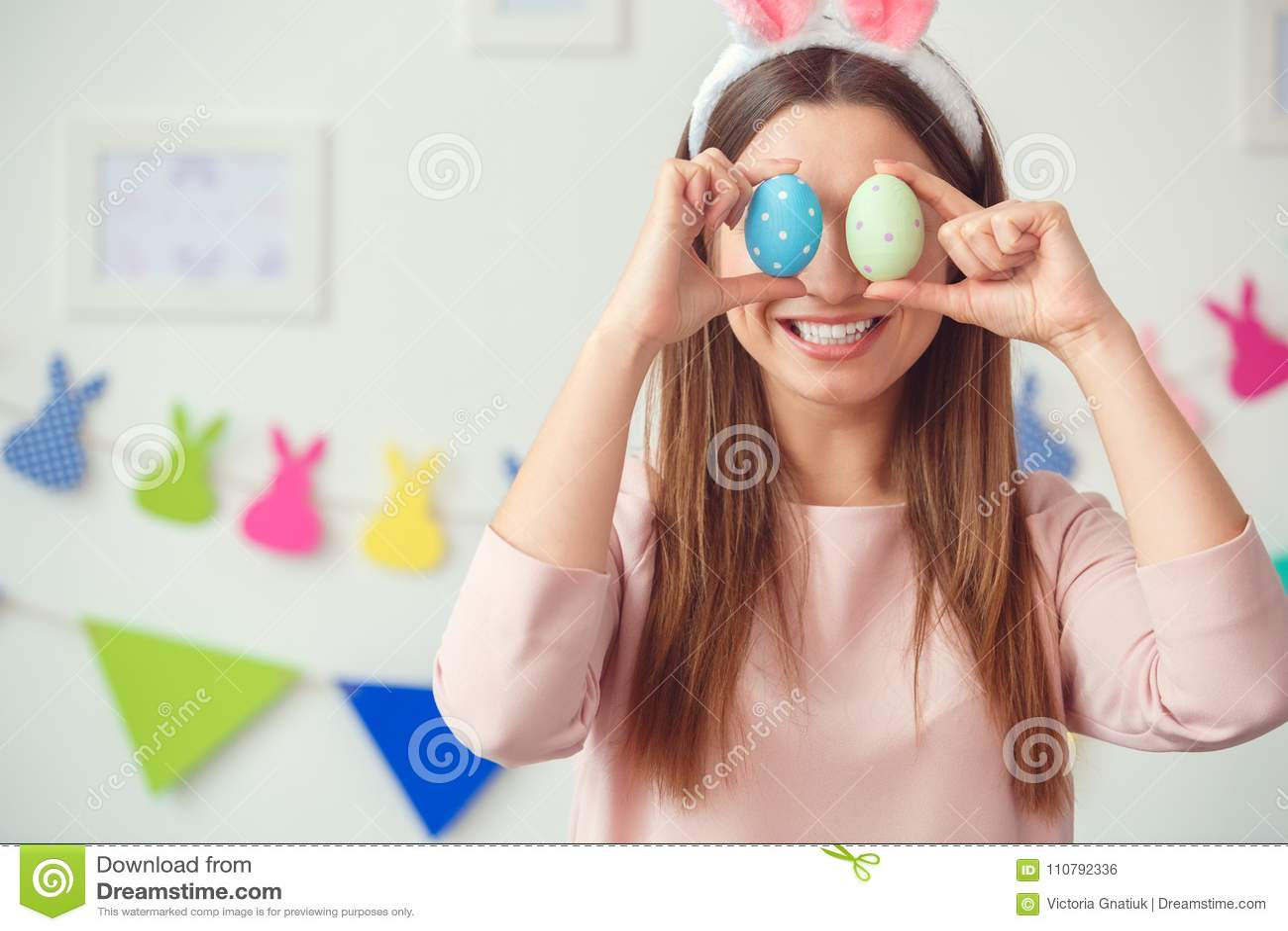 Conceito do celbration de easter da jovem mulher em casa nas orelhas de um coelho que guardam os ovos que cobrem os olhos