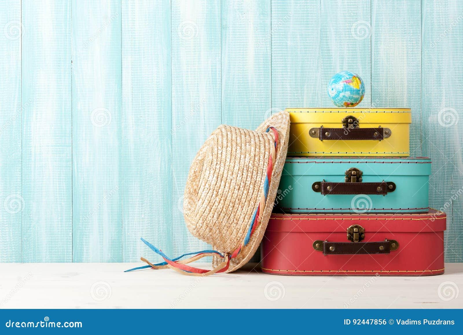 Conceito do curso com as malas de viagem retros do estilo, o chapéu de palha e o globo o