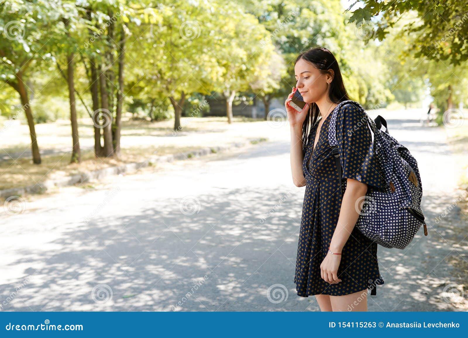 Conceito do curso Mulher ocasional nova com telefone esperto e saco perto do carro de espera da estrada