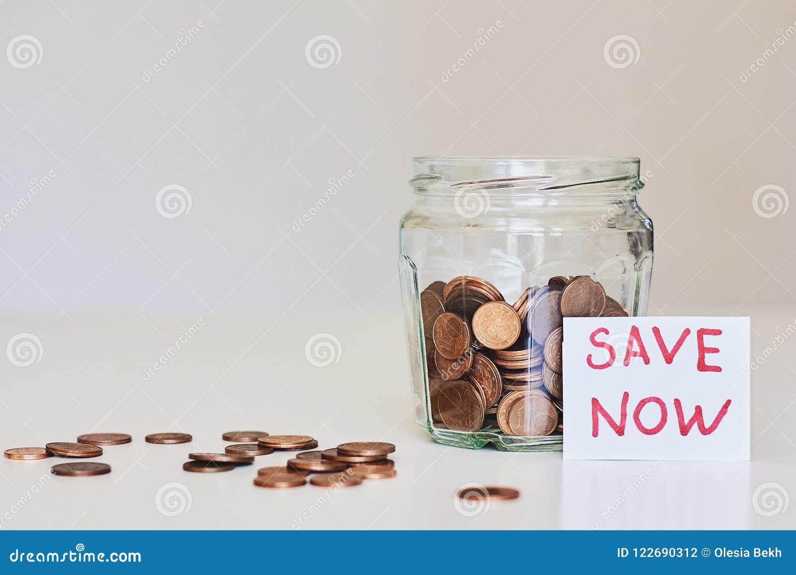 Conceito do dinheiro da economia Frasco de vidro completamente das moedas e das economias do sinal agora