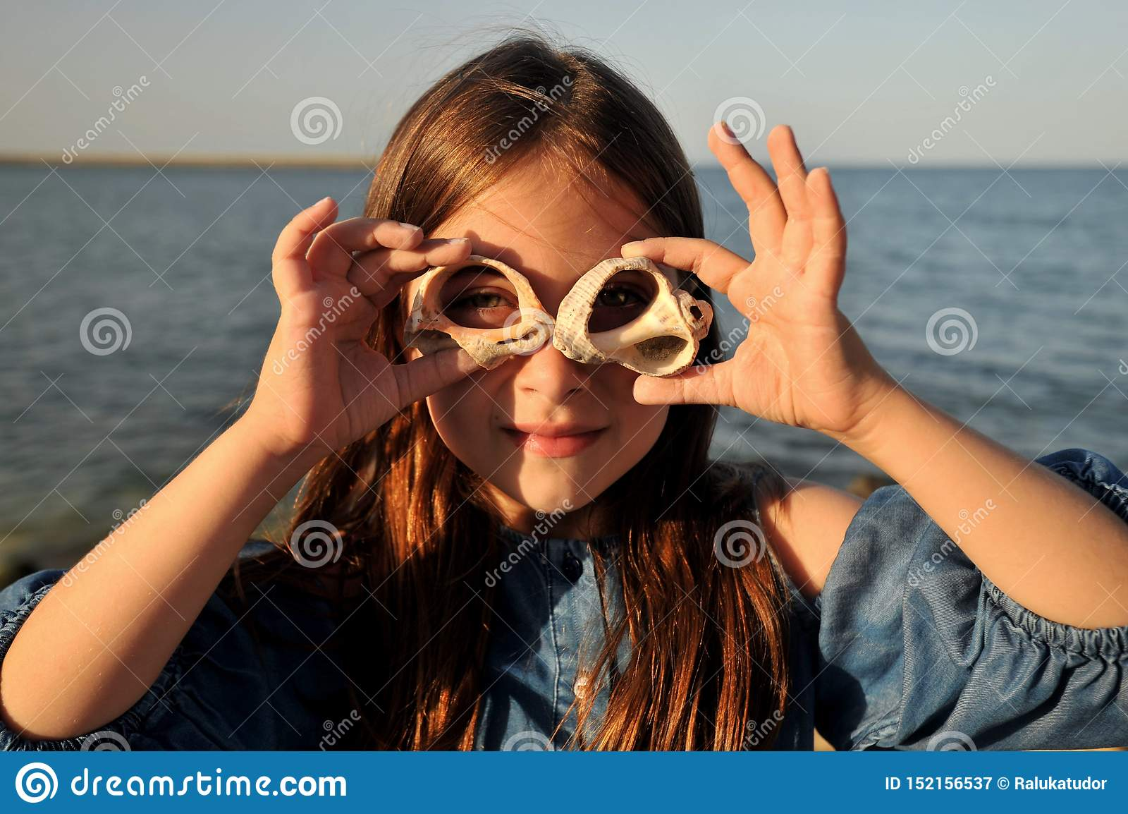Conceito do divertimento do verão com retrato de uma menina com escudos em uma praia