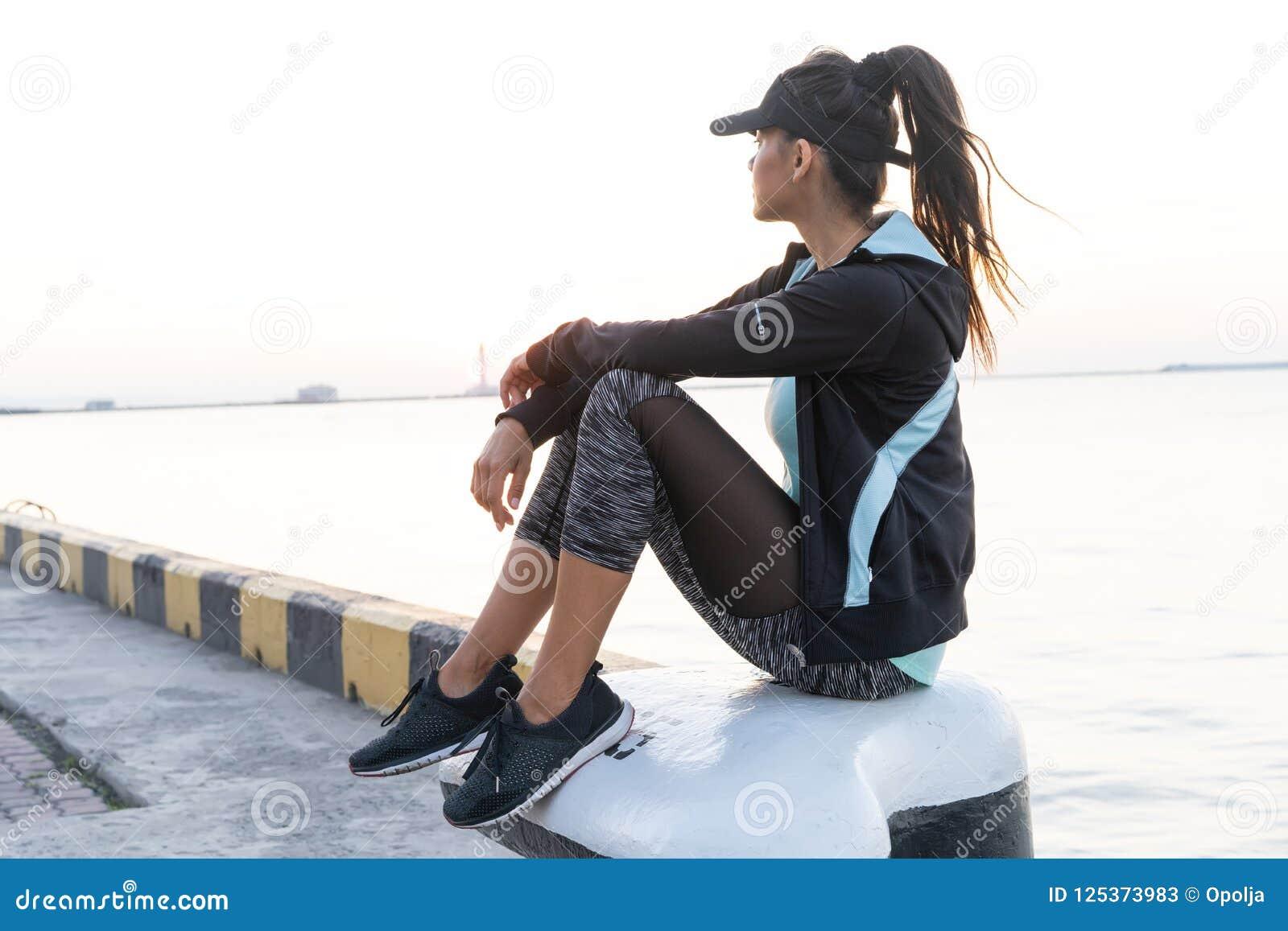 Conceito do esporte e do estilo de vida - a mulher que descansa após fazer ostenta fora