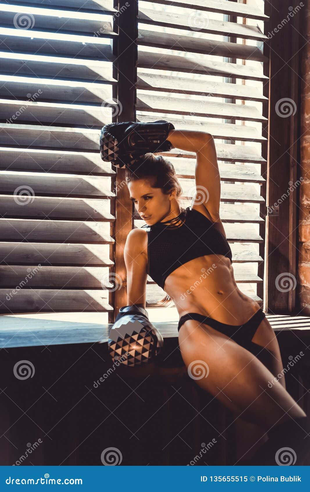 Conceito do exercício do treinamento da força da aptidão - menina  sexy  do esporte do halterofilista muscular que faz exercícios