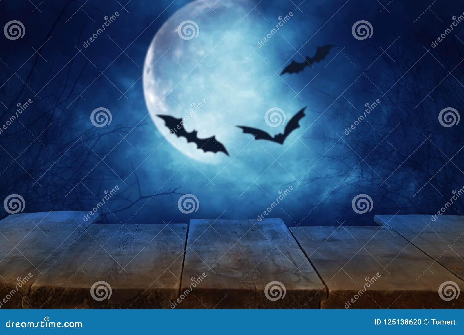 Conceito do feriado de Dia das Bruxas Esvazie a tabela rústica na frente do céu noturno assustador e enevoado com bastões e fundo