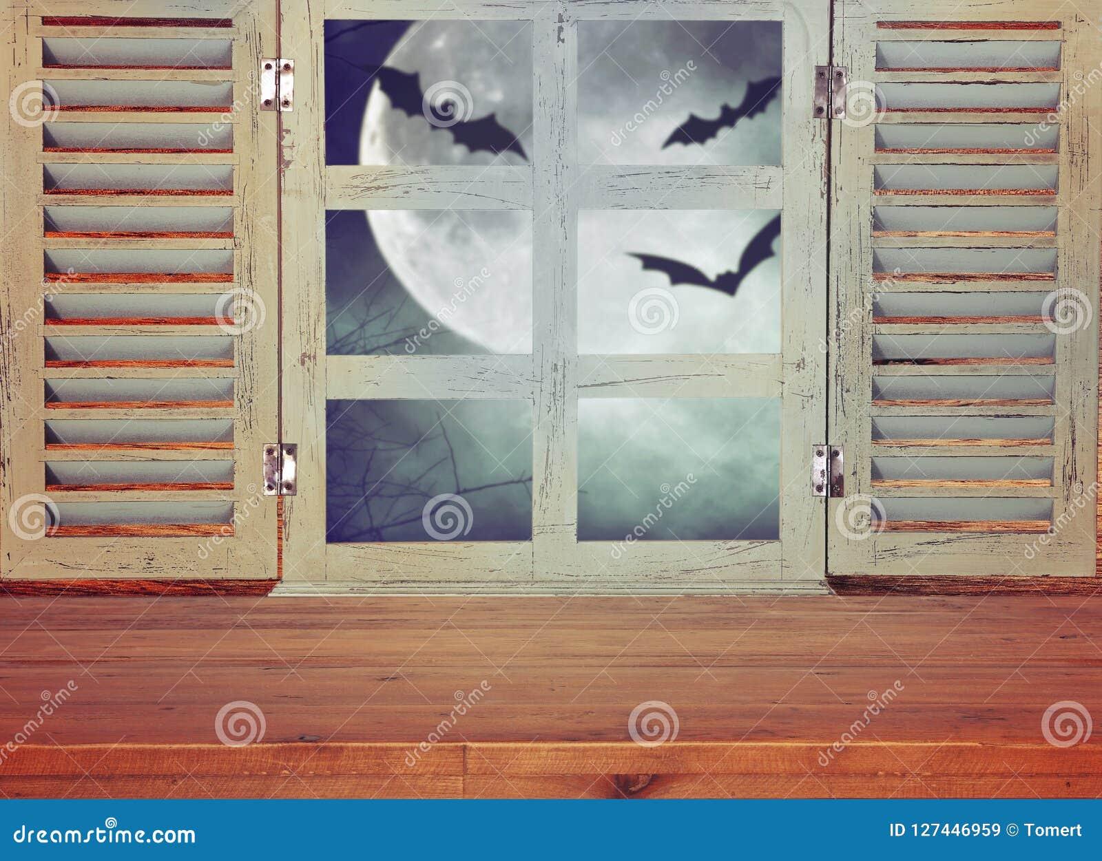 Conceito do feriado de Dia das Bruxas Tabela rústica vazia na frente do fundo assombrado do céu noturno e da janela velha Apronte