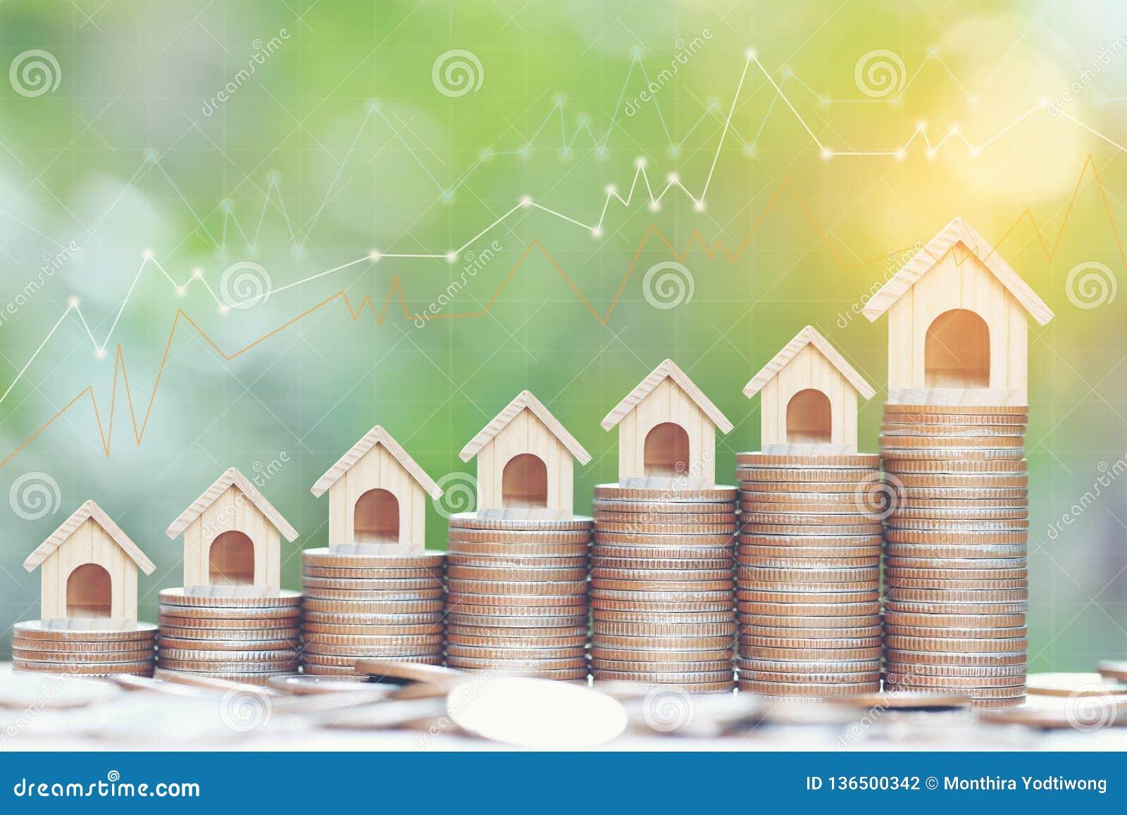 Conceito do investimento empresarial e dos bens imobiliários, casa modelo crescente na pilha de moedas dinheiro e gráfico no fund