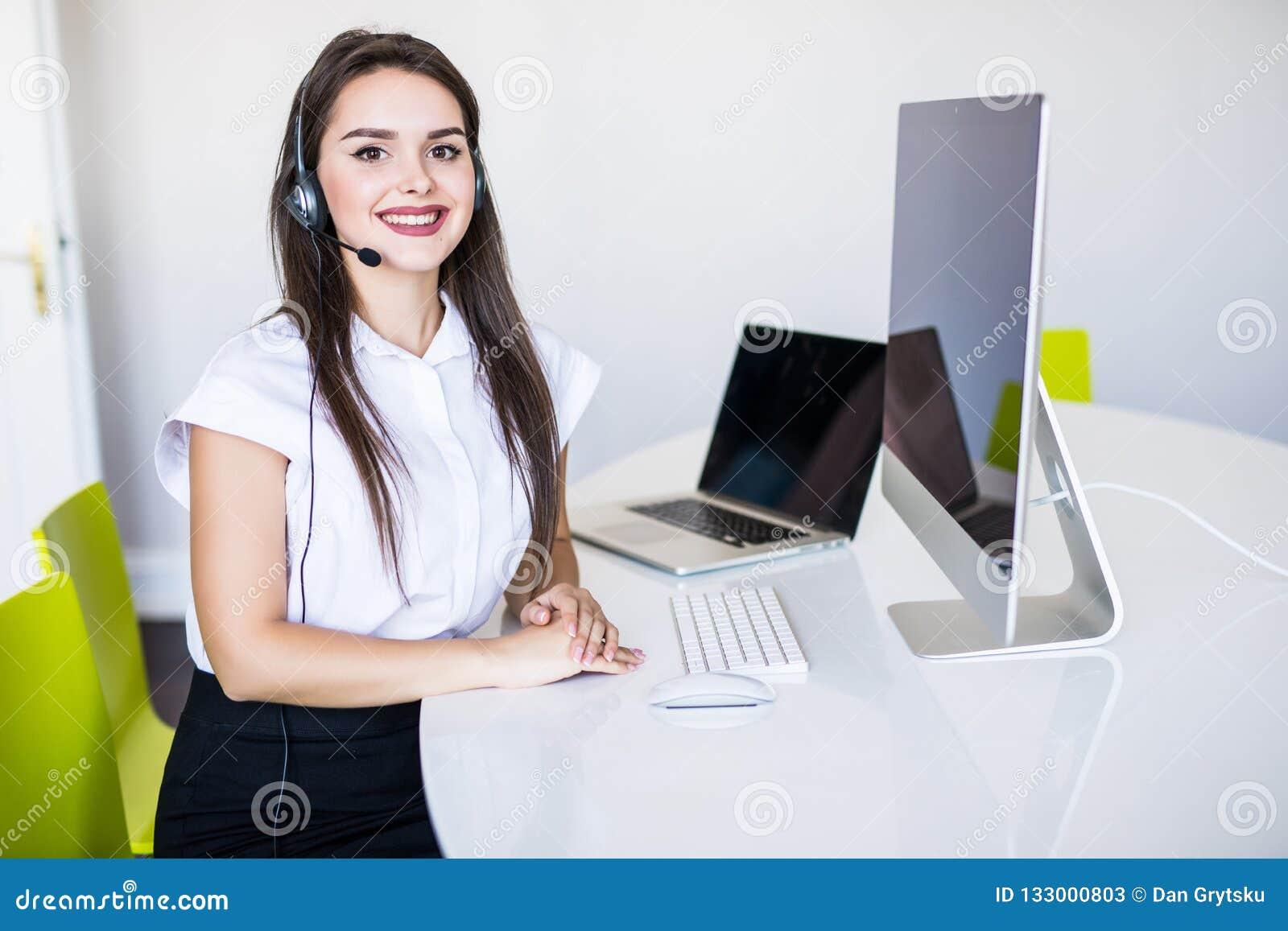 Conceito do negócio, da comunicação, da tecnologia e do centro de atendimento - operador fêmea amigável da linha aberta com fones