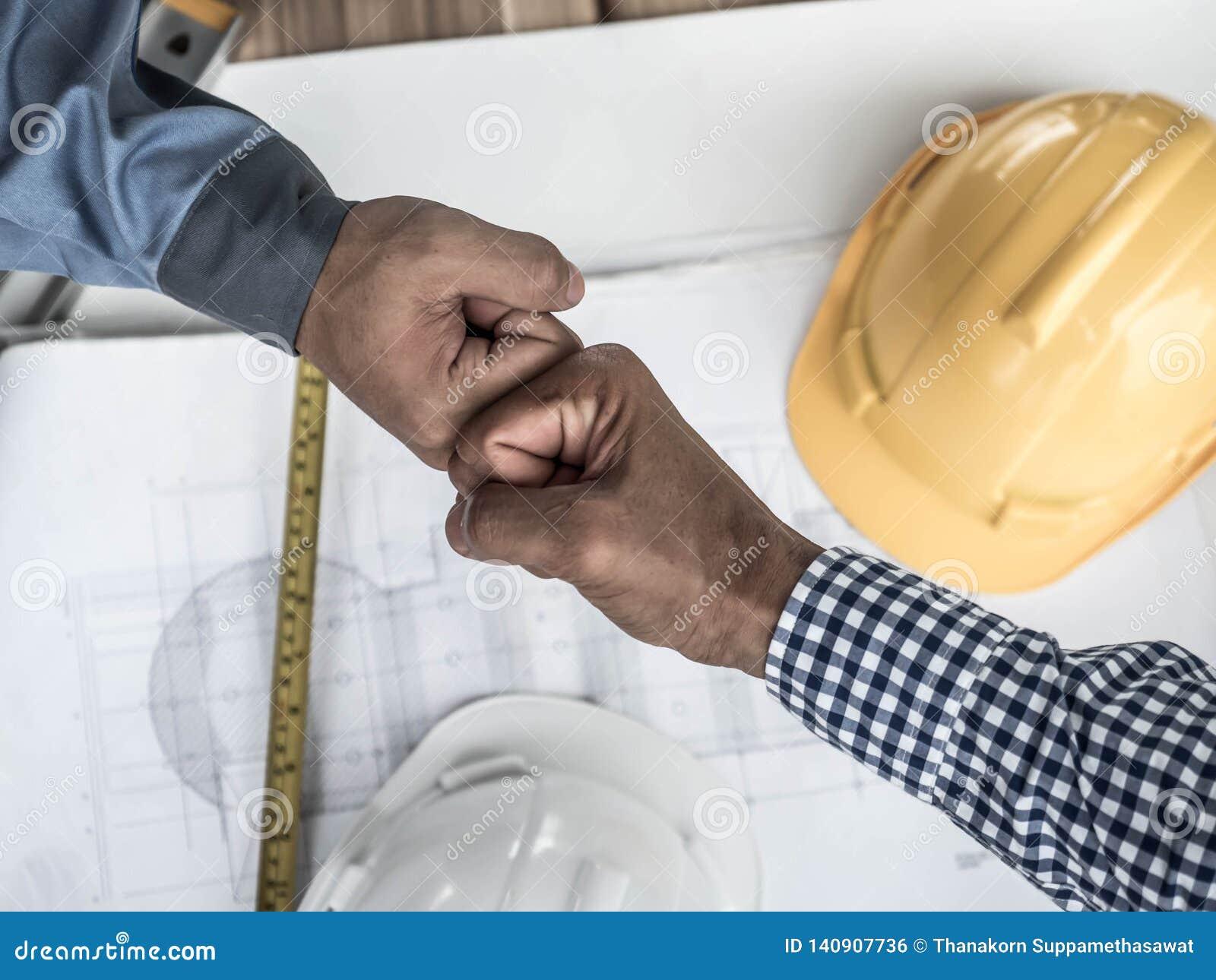 Conceito do negócio, da construção, dos trabalhos de equipe, do gesto e dos povos - grupo de construtores de sorriso nos capacete