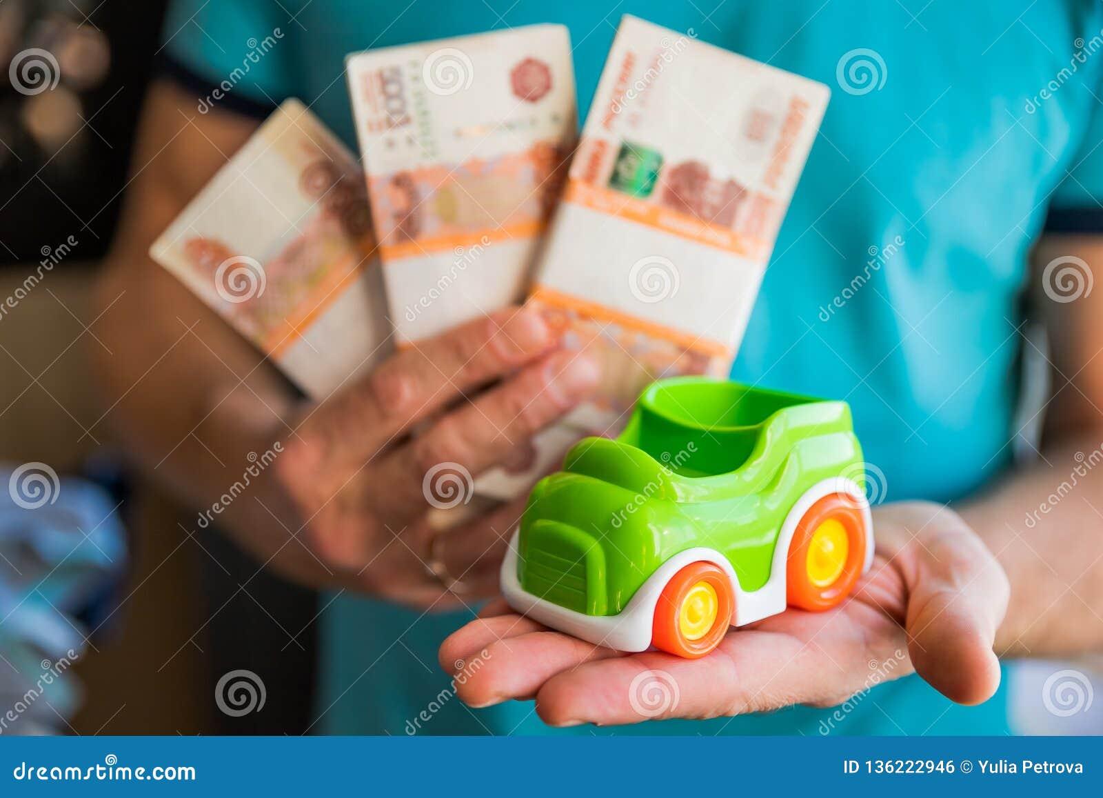 Conceito do negócio, da finança, das economias, da operação bancária ou do empréstimo automóvel Modelo diminuto do carro à dispos