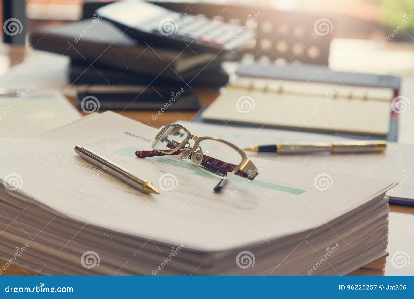 Conceito do negócio e da finança do funcionamento do escritório, dos monóculos do close up e da pena na pilha de original