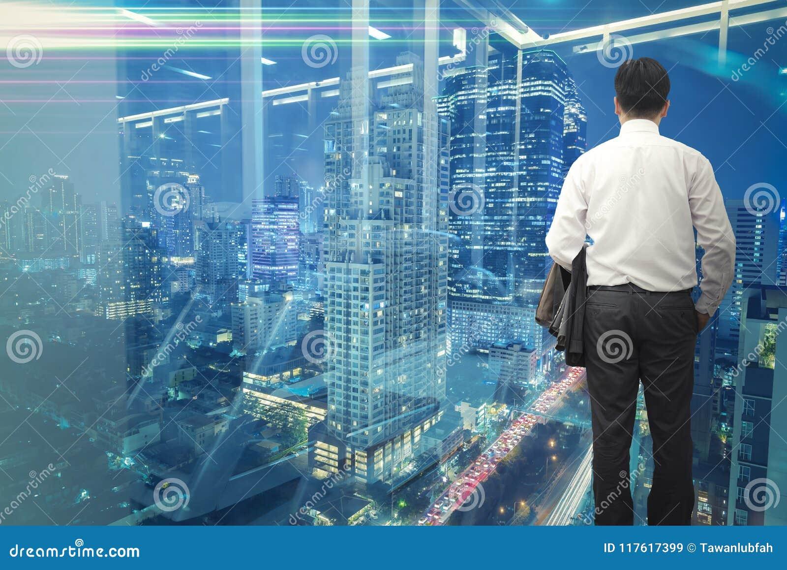 Conceito do negócio Homem de negócio que está e que olha para a frente ao centro da cidade do distrito financeiro fora