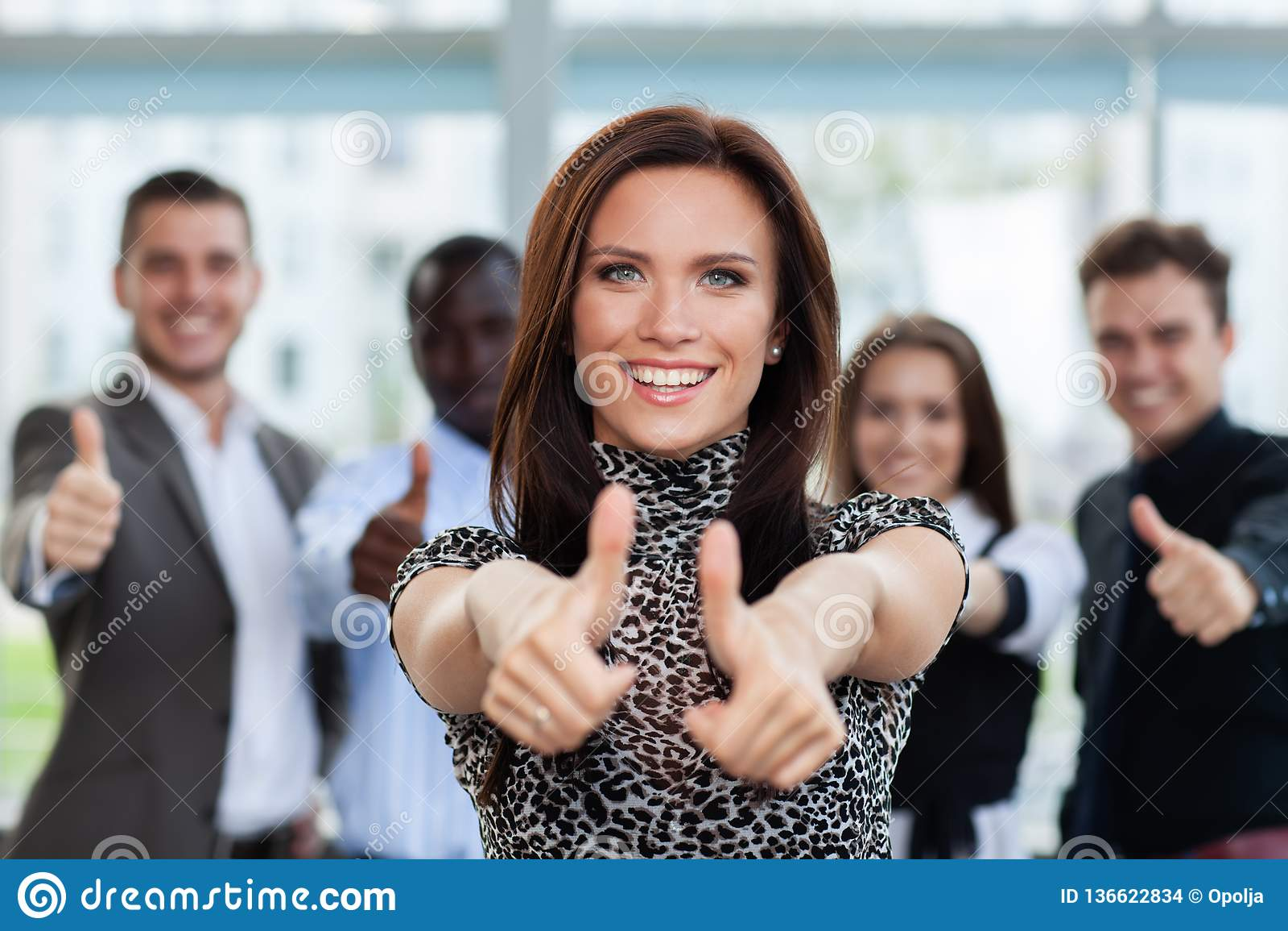 Conceito do negócio - mulher de negócios atrativa com a equipe no escritório que mostra os polegares acima