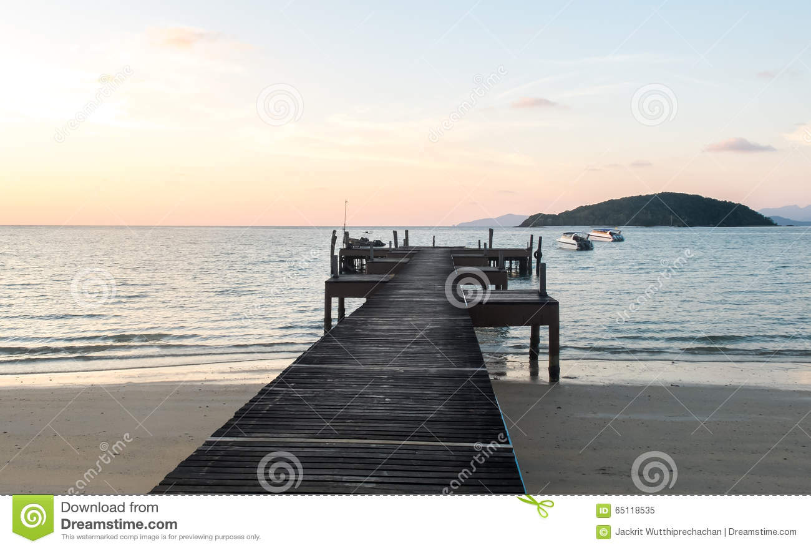 Conceito do tempo de férias, trajeto de madeira macio do filtro de cor do foco entre Crystal Clear Blue Sea e céu