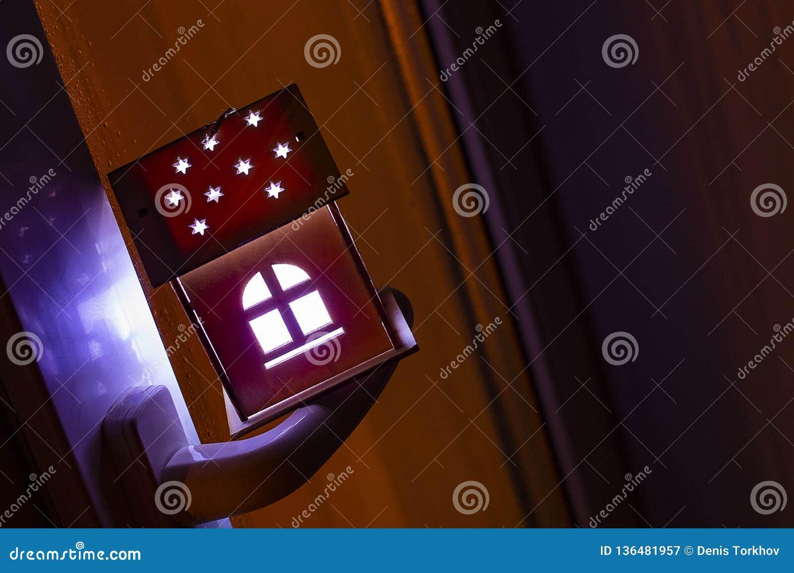 Conceito dos bens imobiliários com uma casa de madeira do brinquedo pequeno no punho de janela A ideia do conceito de bens imobil