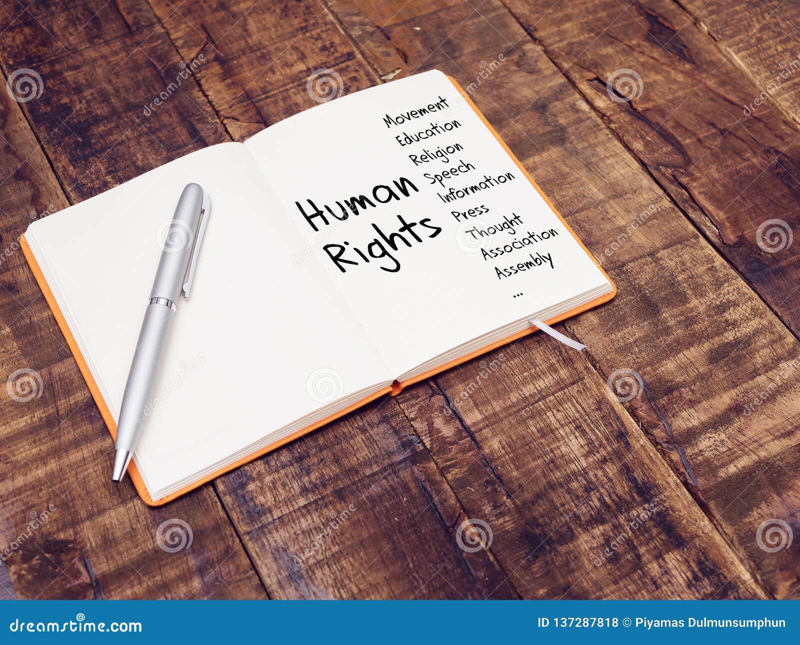 Conceito dos direitos humanos os direitos humanos ocupam-se do mapa com escrita da mão no livro de nota na tabela de madeira