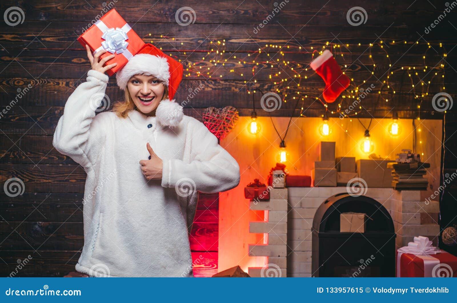 Conceito dos feriados e dos povos de inverno Feliz Natal Mulher do inverno que veste o chapéu vermelho de Papai Noel Preparação d
