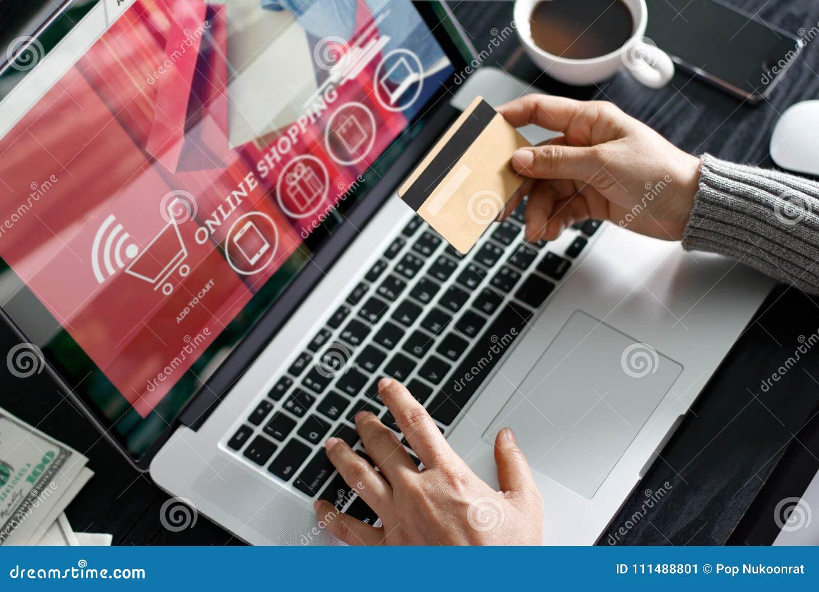 Conceito em linha de compra Mulher que mantém o cartão de crédito do ouro compra disponivel e em linha usando-se no portátil em c