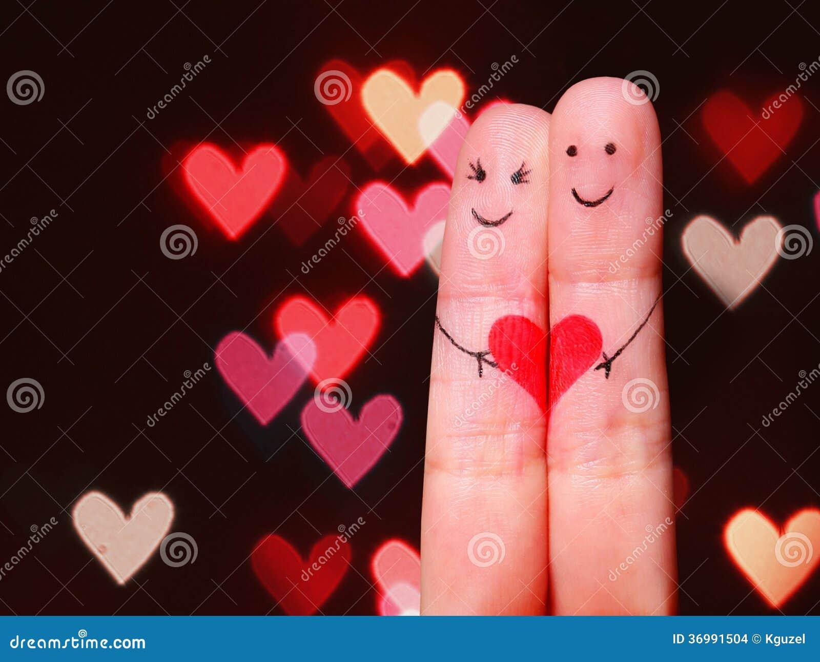 Conceito feliz dos pares. Dois dedos no amor com smiley pintado
