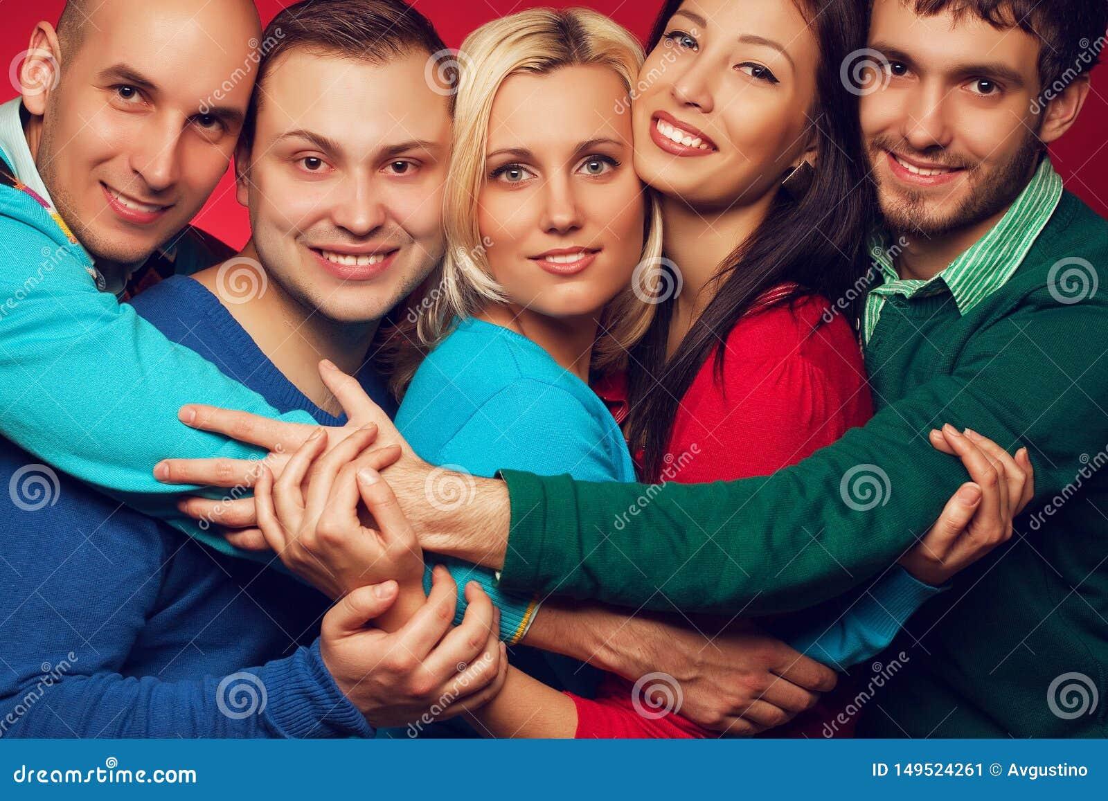 Conceito feliz dos povos Retrato de cinco amigos próximos à moda que abraçam, sorrindo e levantando junto