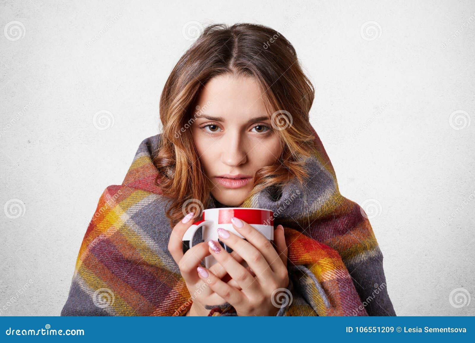 Conceito frio da doença do inverno A mulher bonita de congelação envolvida na cobertura quadriculado morna da manta, bebida quent