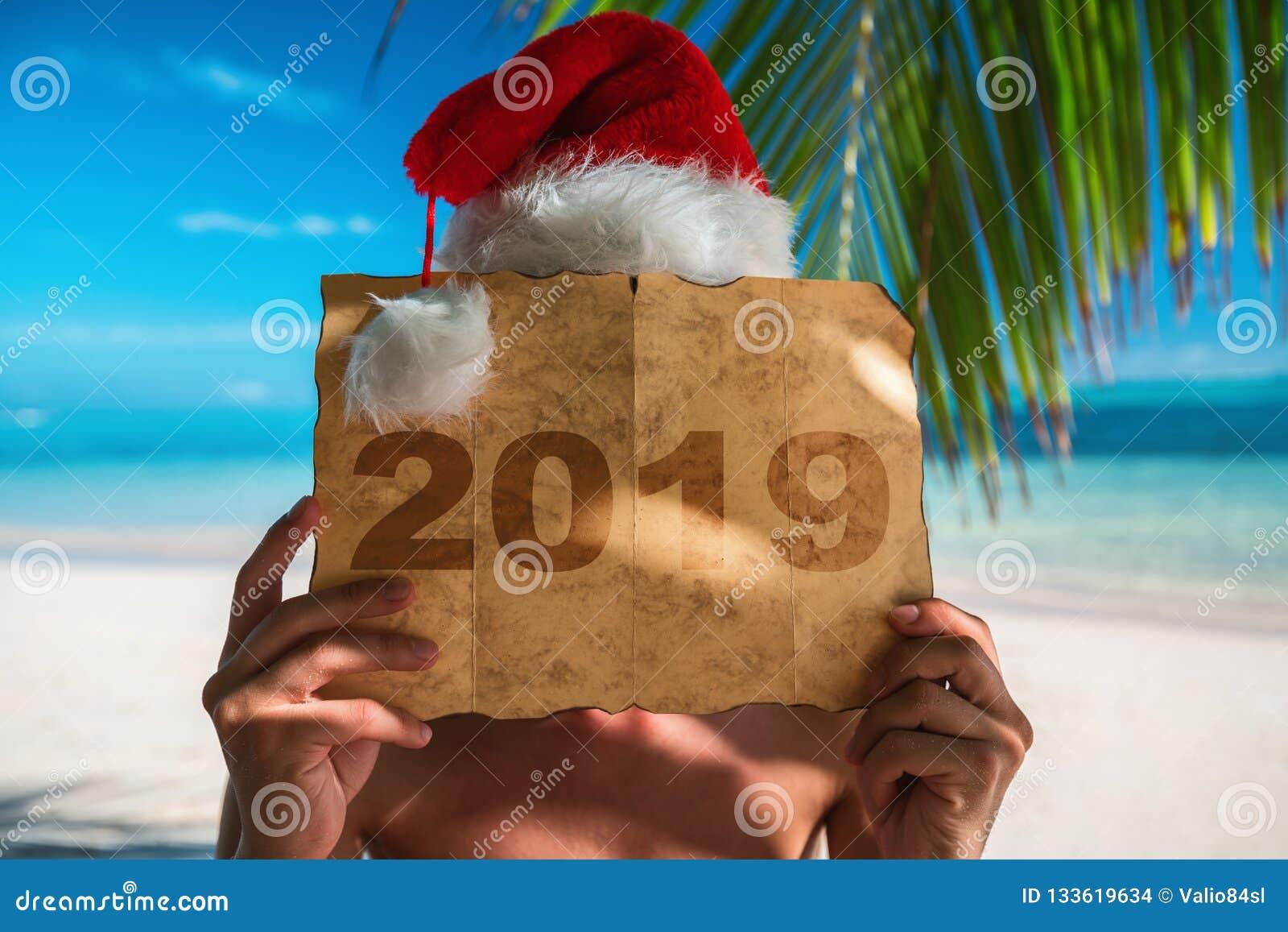 Conceito 2019 Homem do turista com o chapéu de Santa Claus que relaxa no tropi
