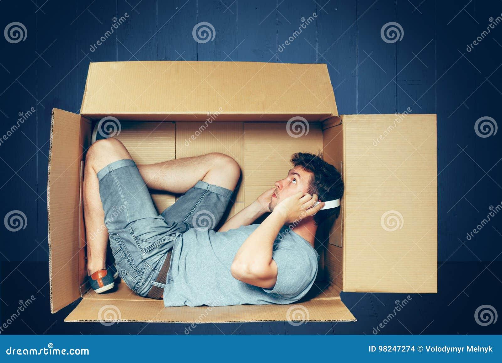 Conceito introvertido O homem que senta-se dentro da caixa e que trabalha com portátil