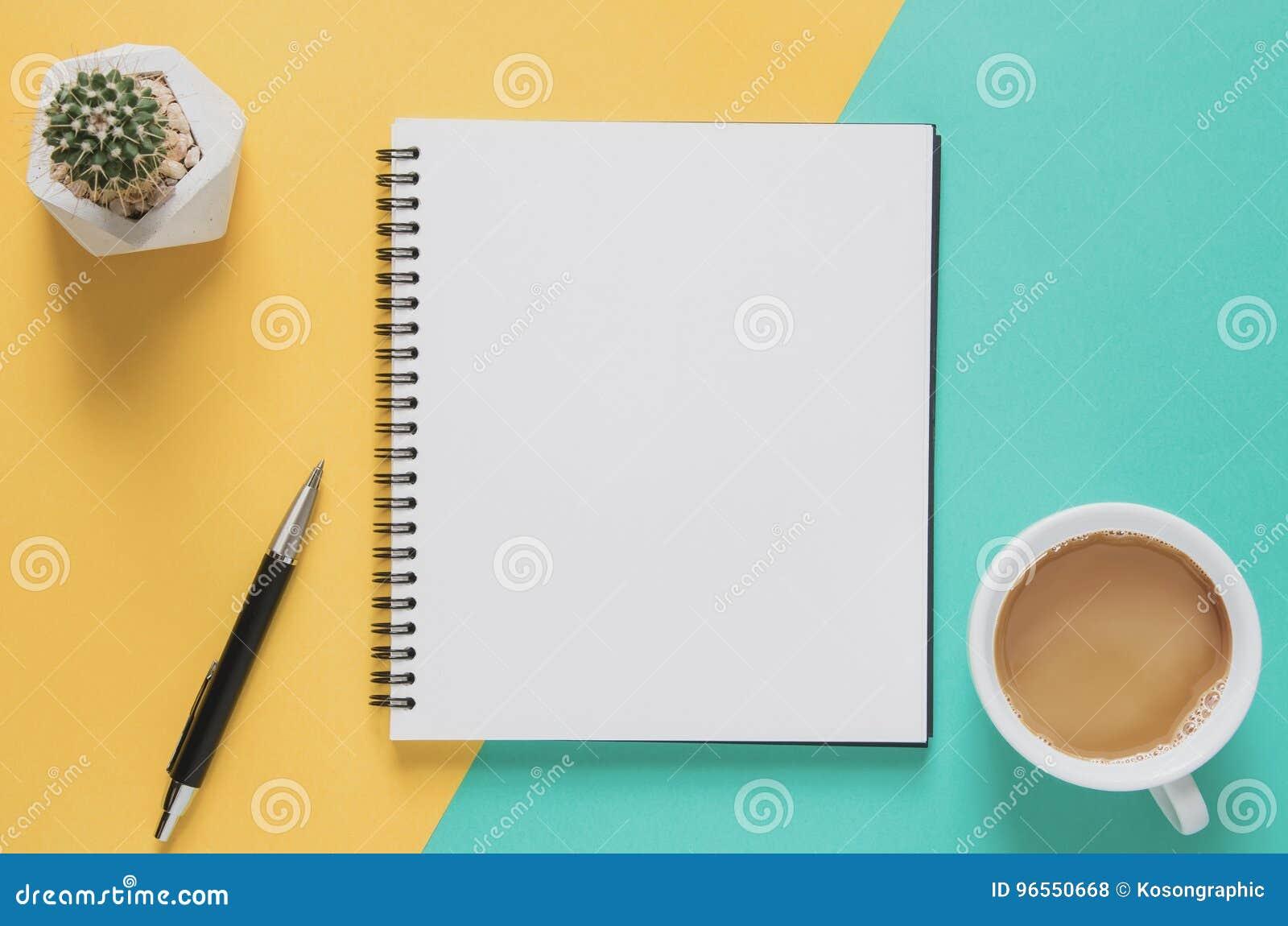 Conceito mínimo do local de trabalho do escritório Caderno vazio com xícara de café, cacto, lápis no fundo amarelo e azul