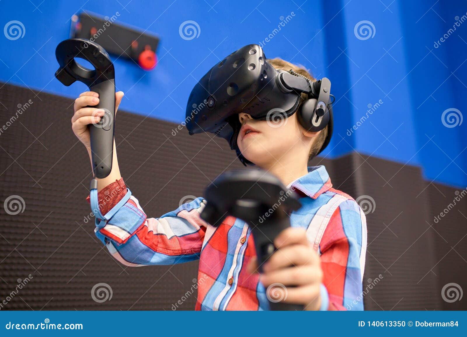 Conceito moderno da tecnologia, do jogo e dos povos - menino nos auriculares da realidade virtual ou nos vidros 3d que jogam o vi