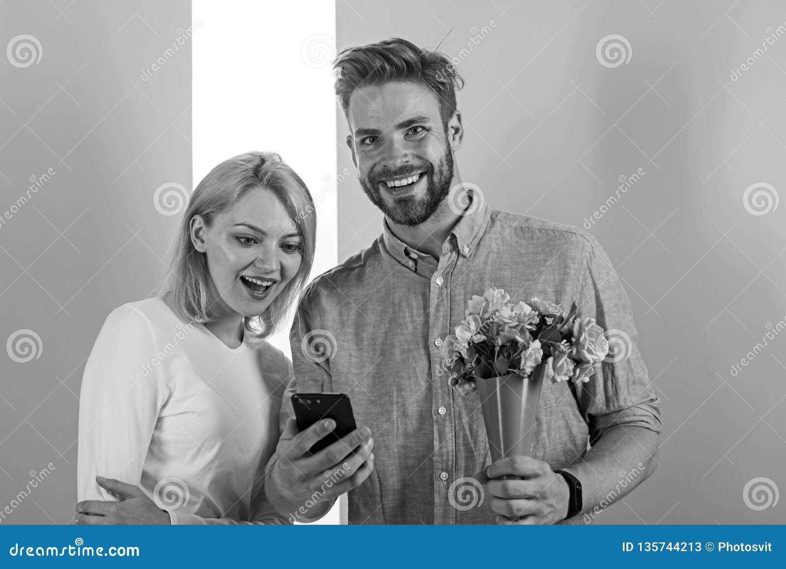 Conceito romântico Pares no amor interessado pelo telefone O homem mostra a foto no smartphone à menina, memórias doces do seu