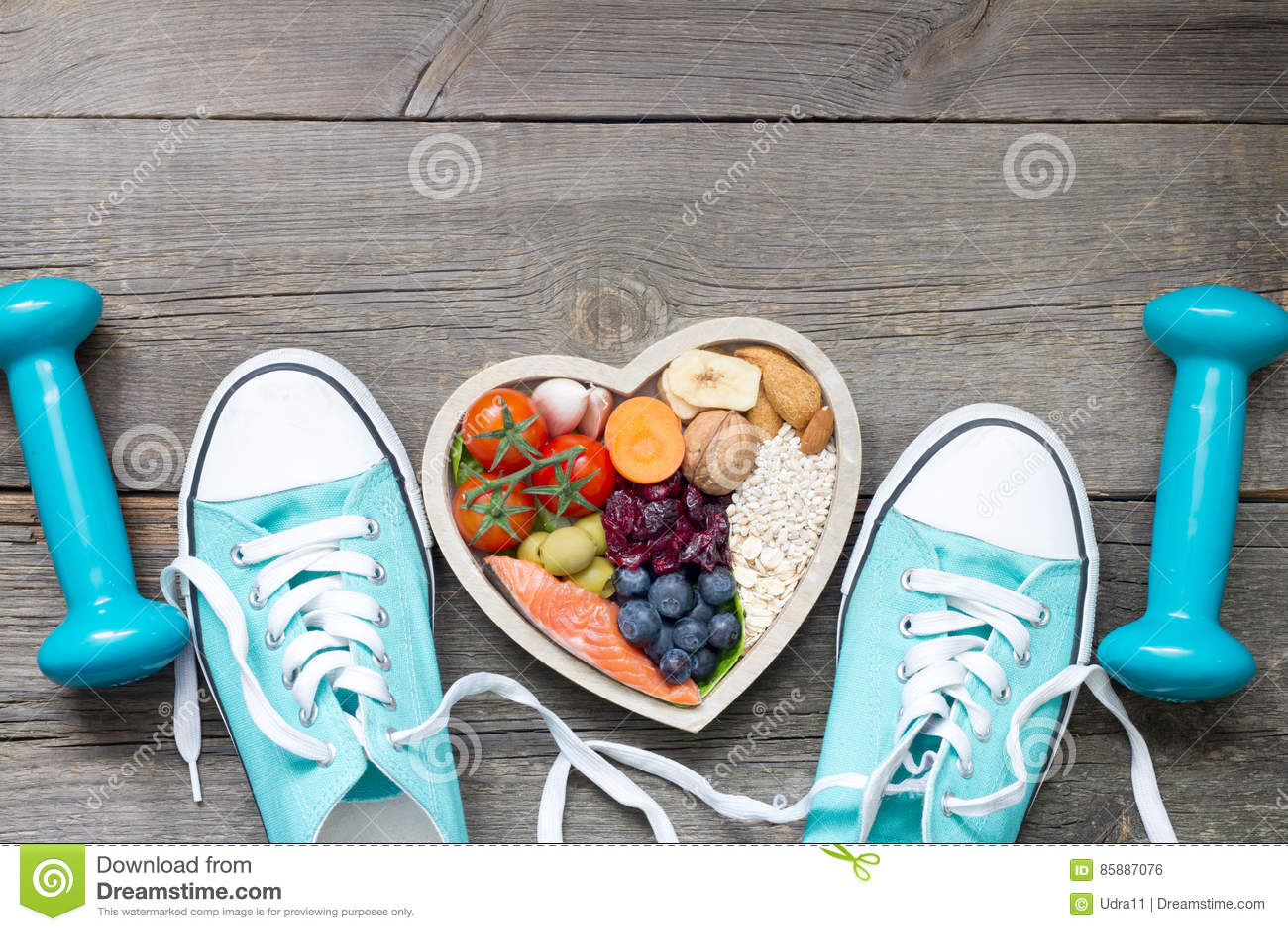 Conceito saudável do estilo de vida com alimento em acessórios da aptidão do coração e dos esportes
