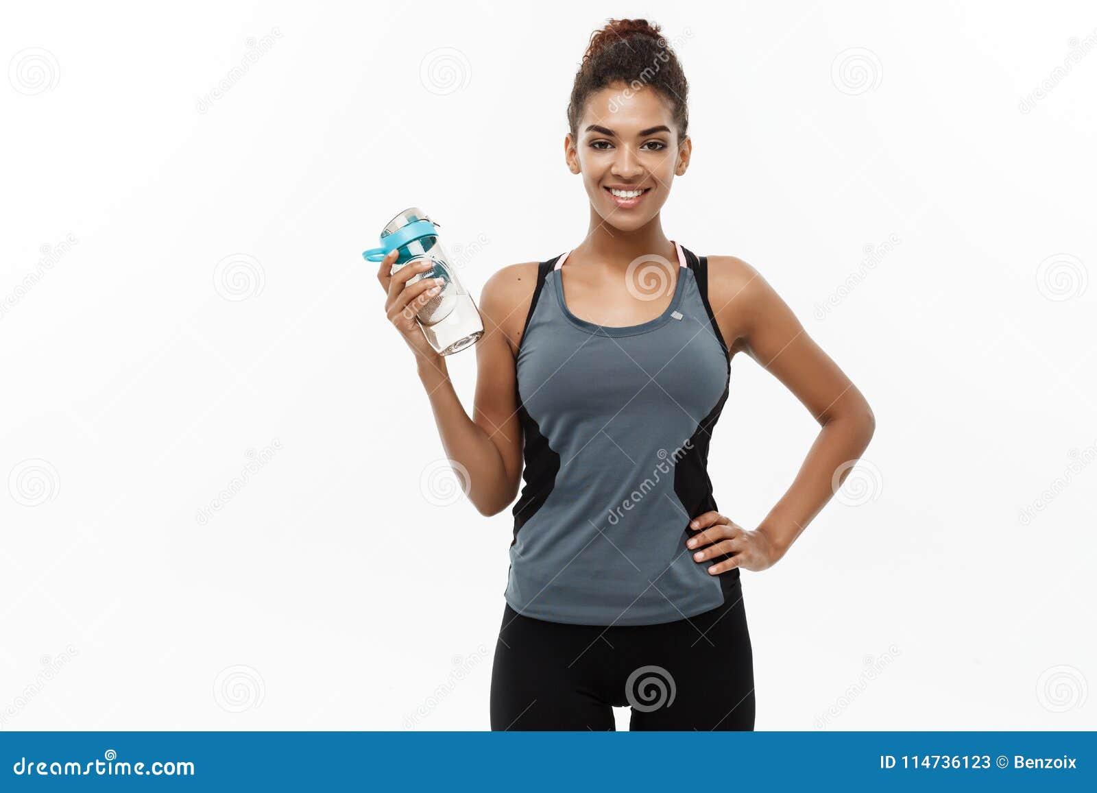 Conceito saudável e da aptidão - a menina afro-americano bonita no esporte veste guardar a garrafa de água após o exercício