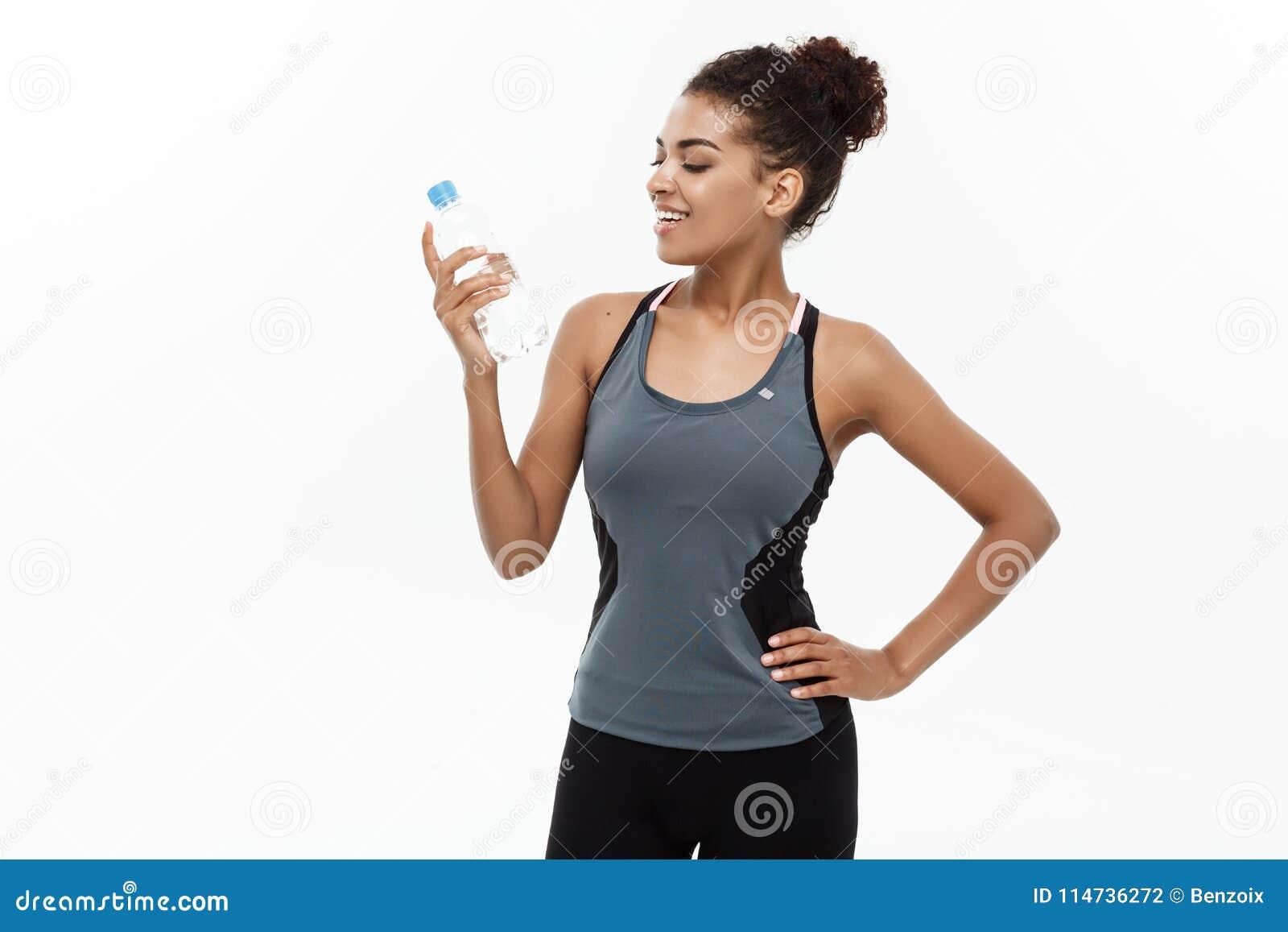 Conceito saudável e da aptidão - a menina afro-americano bonita no esporte veste guardar a garrafa de água plástica em seguida