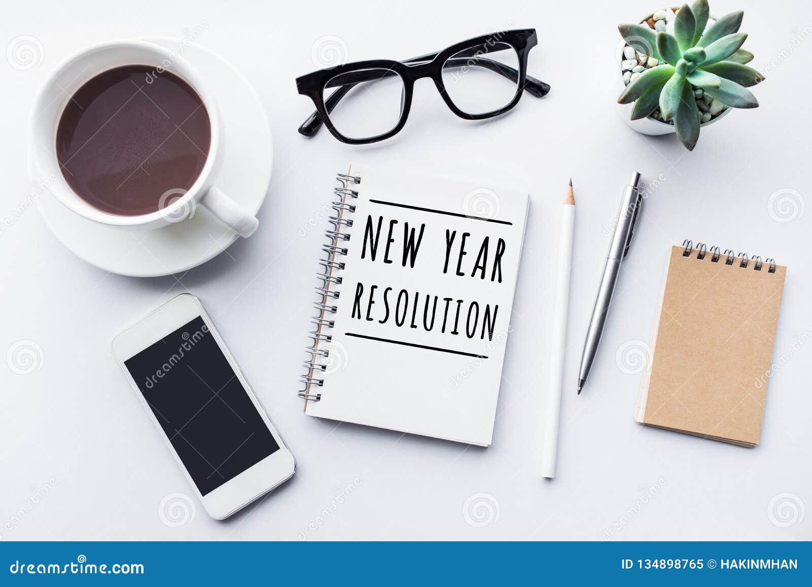 Conceitos da definição do ano novo com texto no caderno e na tabela do escritório dos acessórios