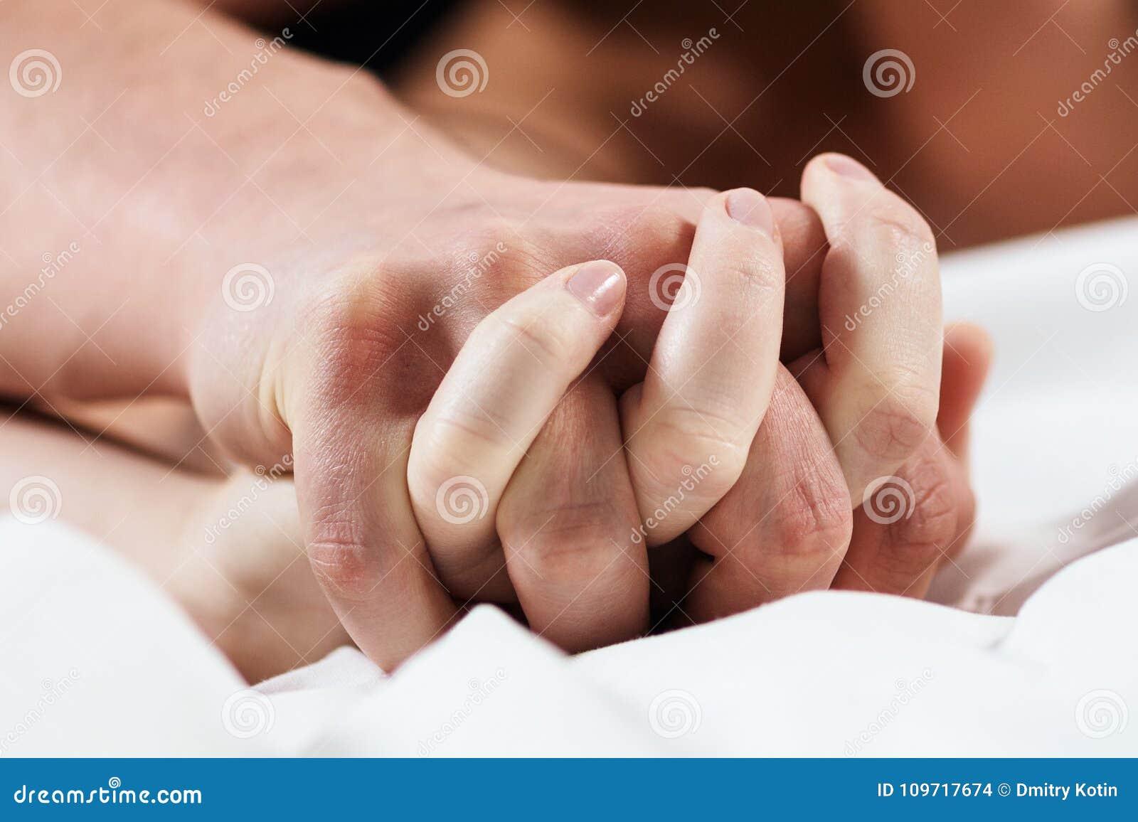 Concentré sur des mains des couples de passion ayant le sexe