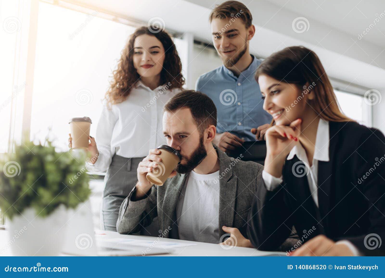 Concentración completa en el trabajo Grupo de hombres de negocios jovenes que trabajan y que comunican mientras que se sienta en