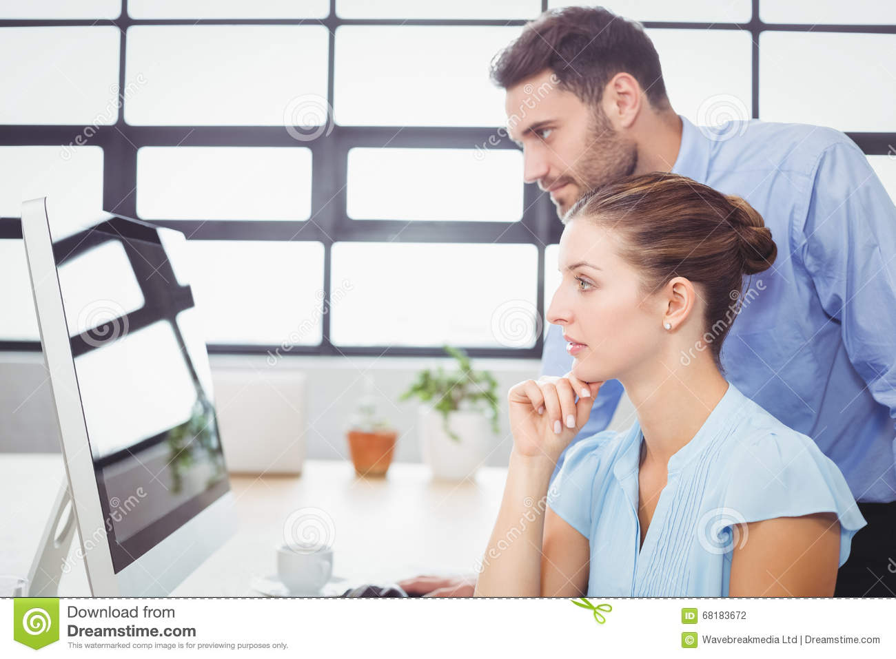 Stock Photo: Concentrated business people looking at computer monitor
