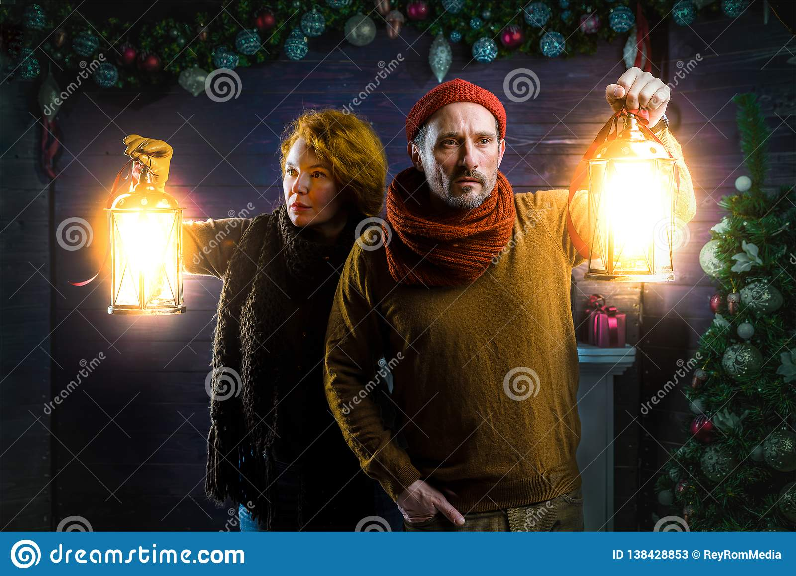 Concentrated couple scrutinizing the house while using hand lanterns