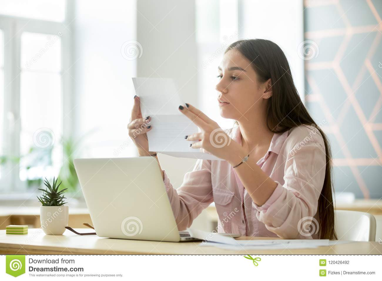 Concentrated Female Employee Reading Business Contract In Office