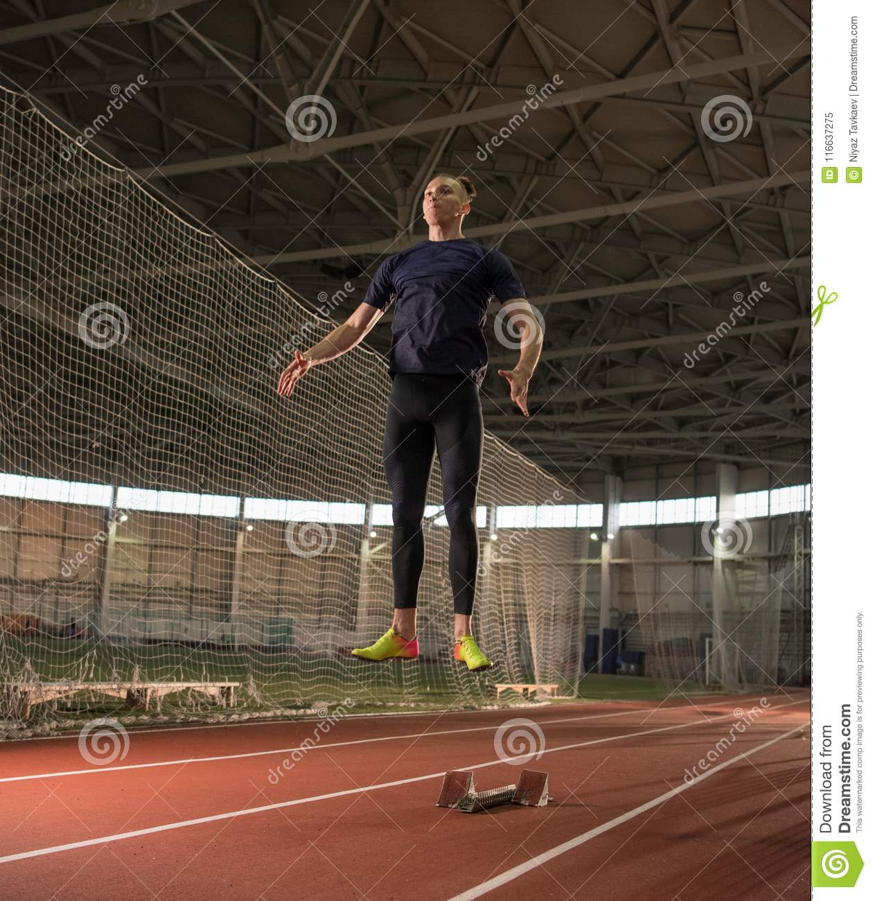 Concentrated Male Track And Field Athlete Warming Up Before Hurdling