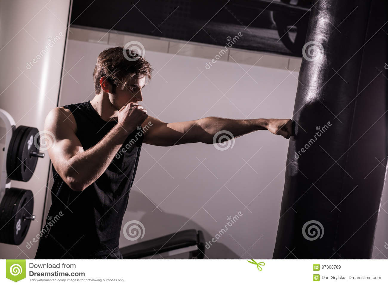 Concentrated muscular kickbox fighter exercising with punch bag on white in gym