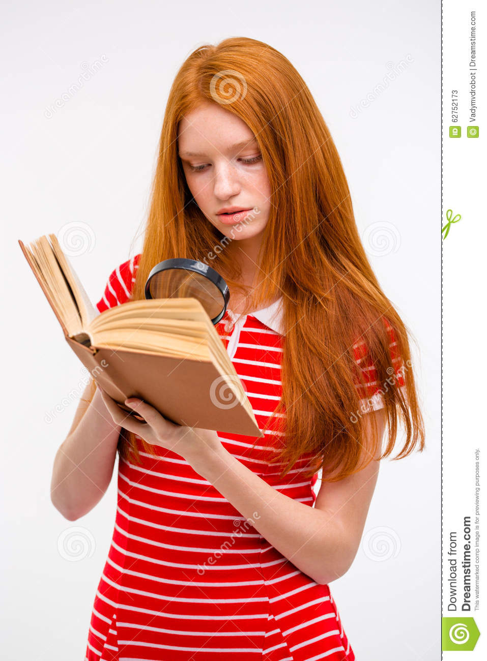 Concentrated Redhead Young Female Reading Book Using