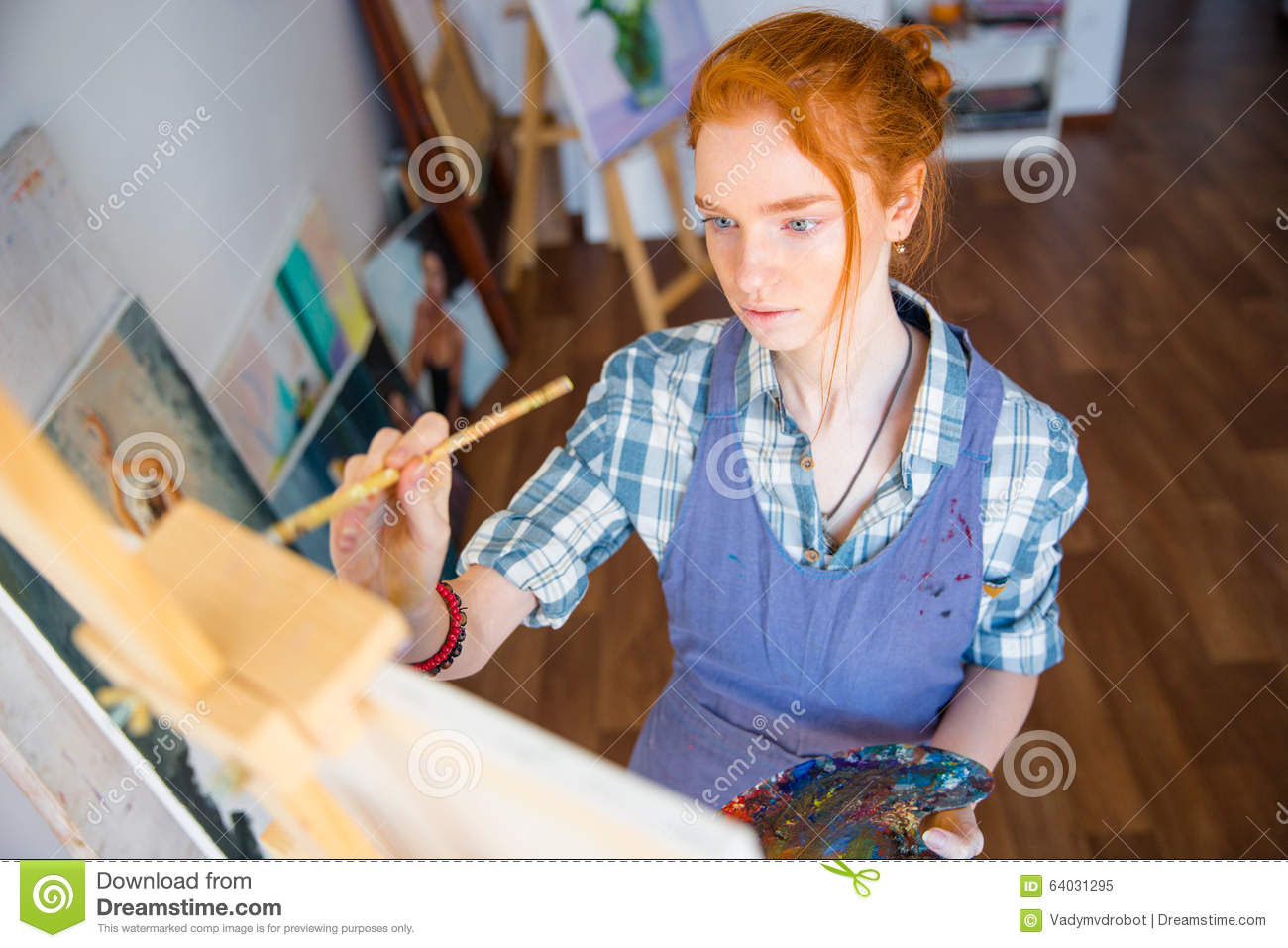 Concentrated woman painter holding art palette and painting on canvas