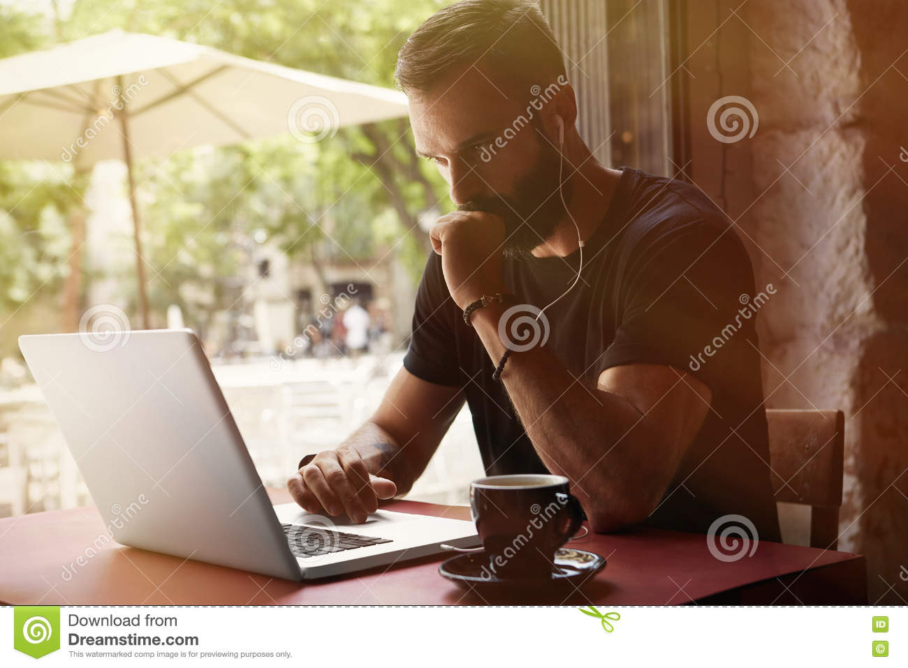 Concentrated Young Bearded Businessman Wearing Black Tshirt Working Laptop Urban Cafe.Man Sitting Table Cup Coffee