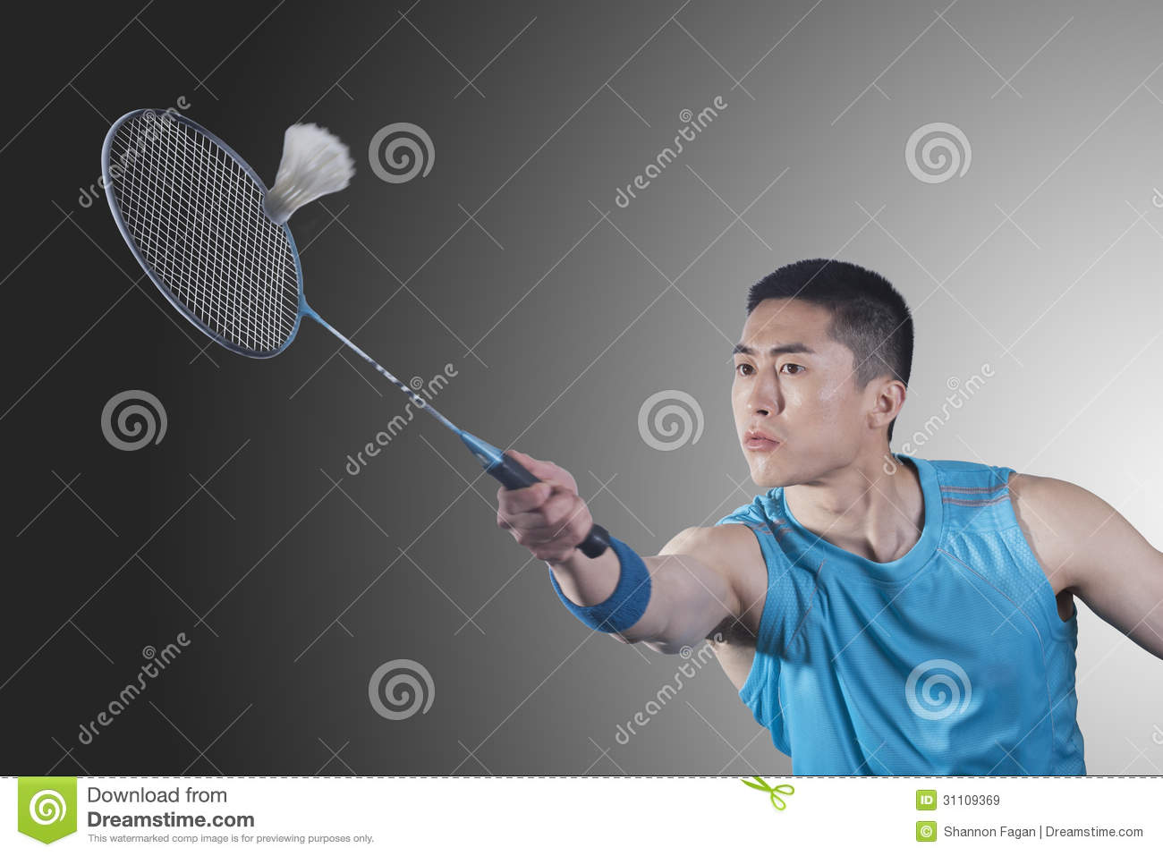 Concentrated Young man playing badminton, hitting