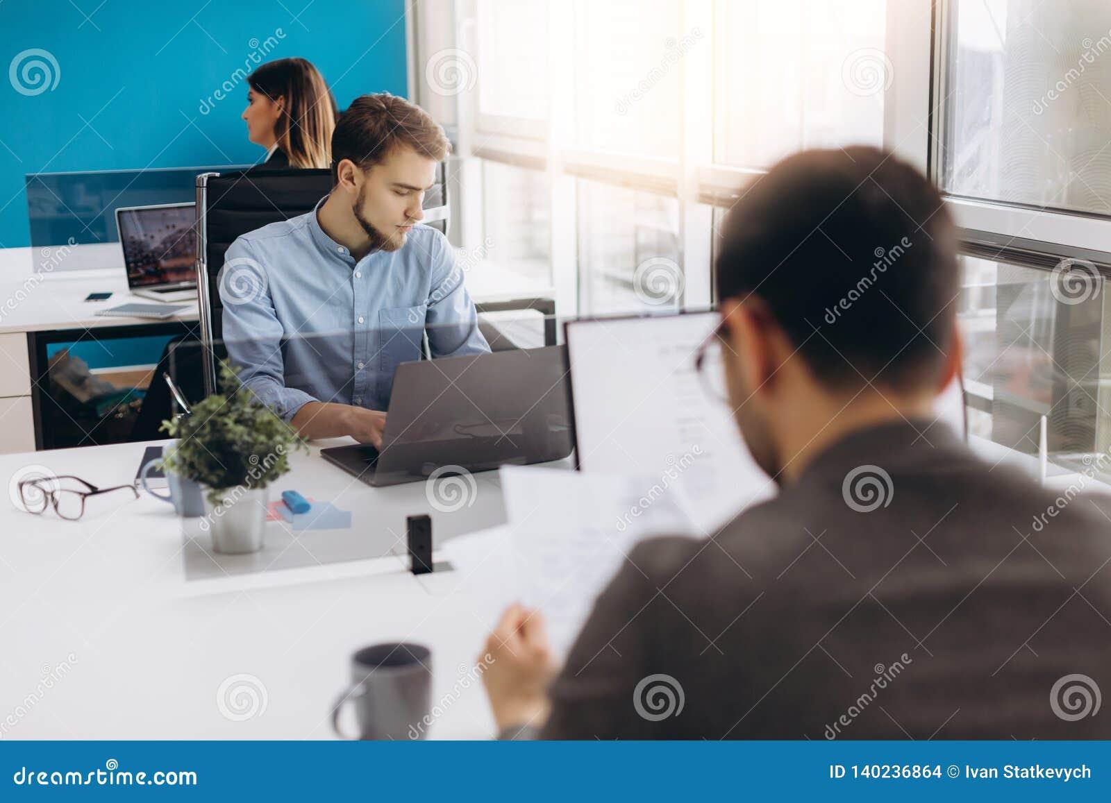 Concentrato su lavoro Giovane uomo concentrato della barba che lavora al computer portatile mentre sedendosi al suo posto di lavo