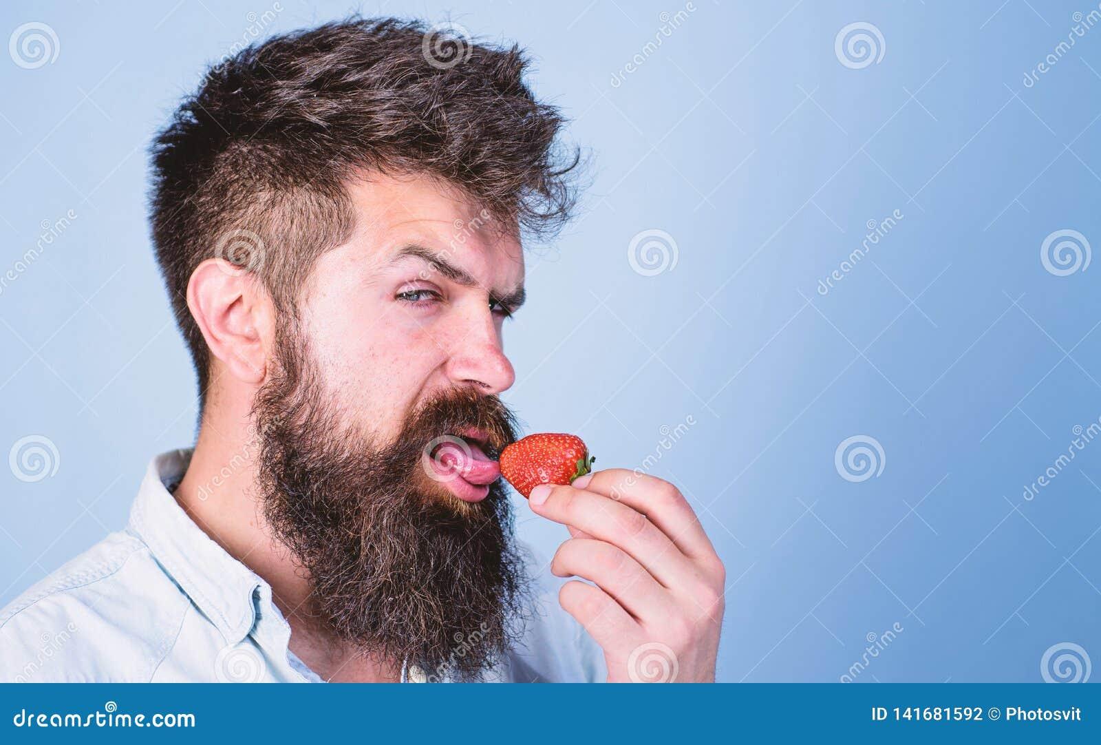 Concept érotique Plaisir oral C est comment été de goûts Équipez le hippie sexy beau avec la longue barbe léchant la fraise