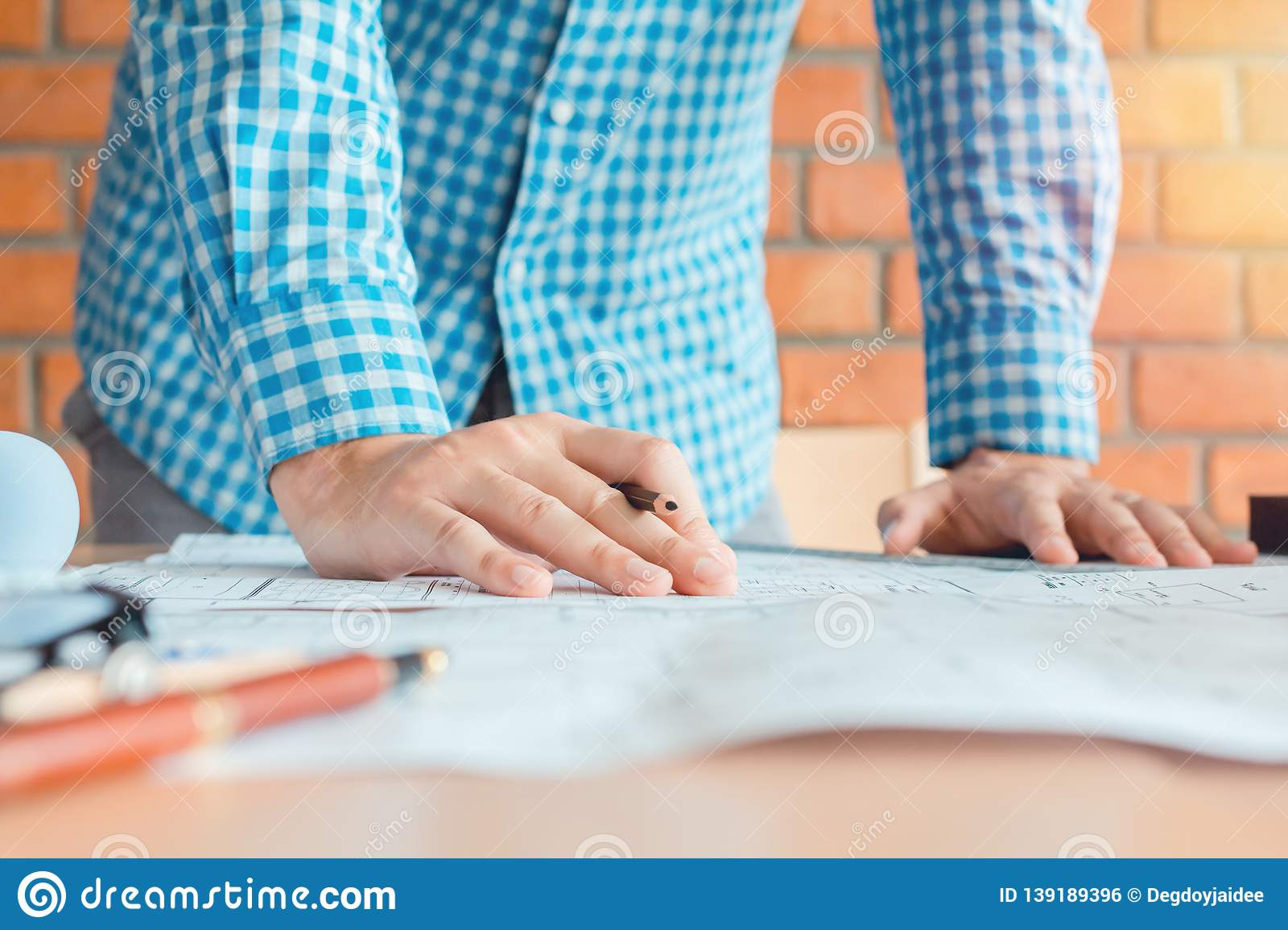 Concept architects,engineer holding pen pointing equipment architects On the desk with a blueprint in the office, Vintage