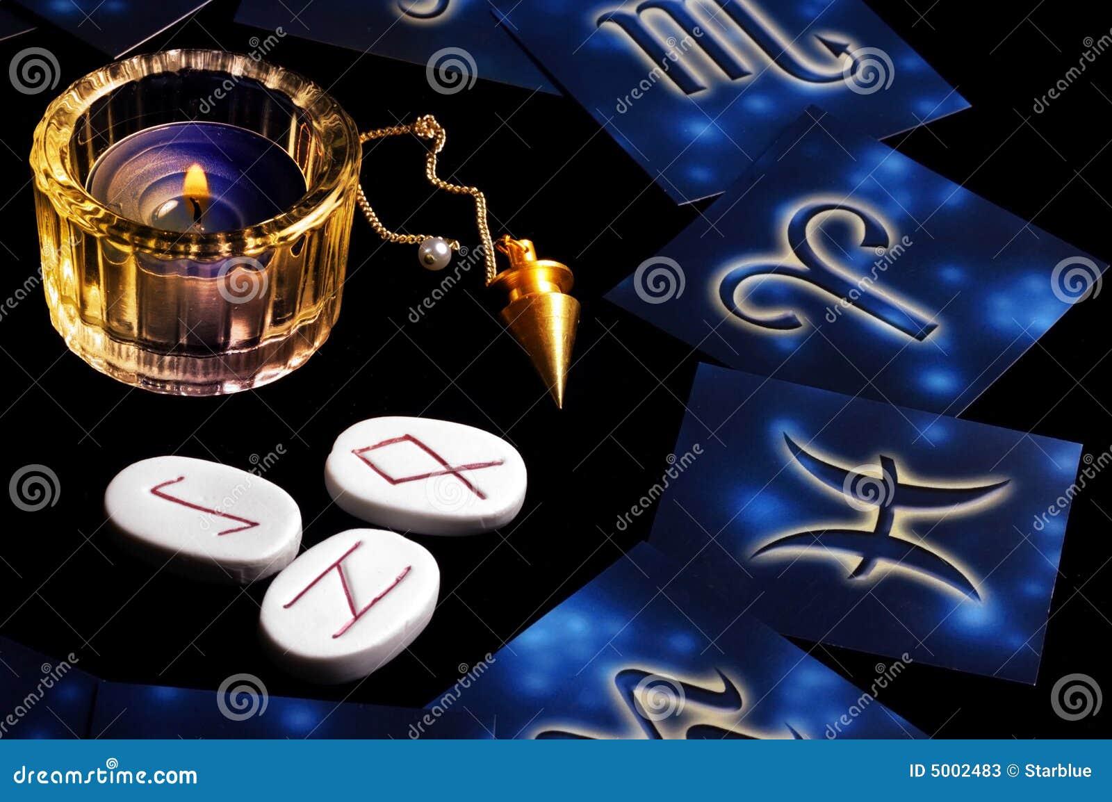 Cartes zodiacales bleues en cercle autour d une bougie, des runes et d un pendule  magique acf1af29f8a